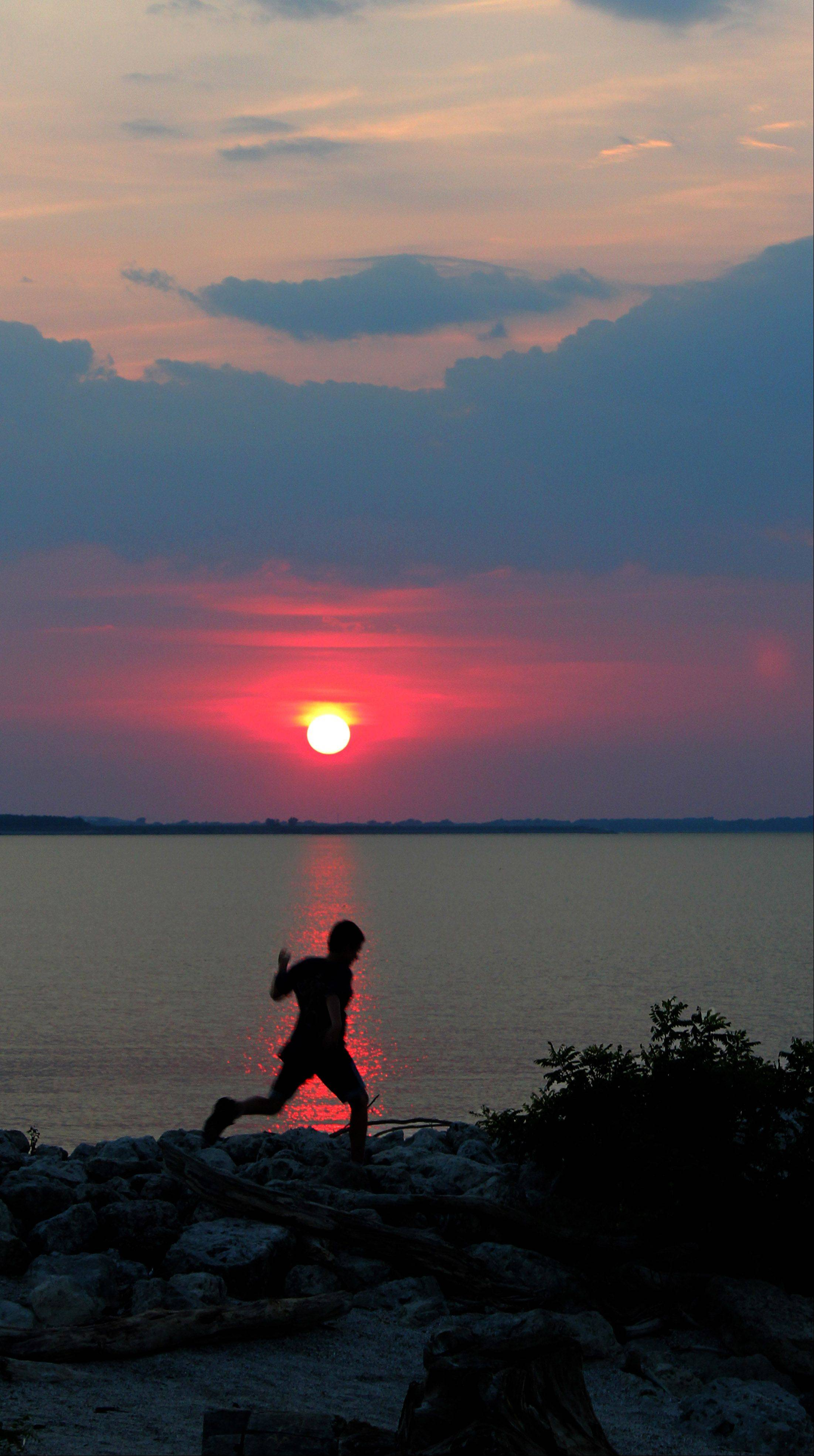 Dane Whitney, of Libertyville, jumps along the shore at sunset during vacation at Maumee Bay in Ohio.