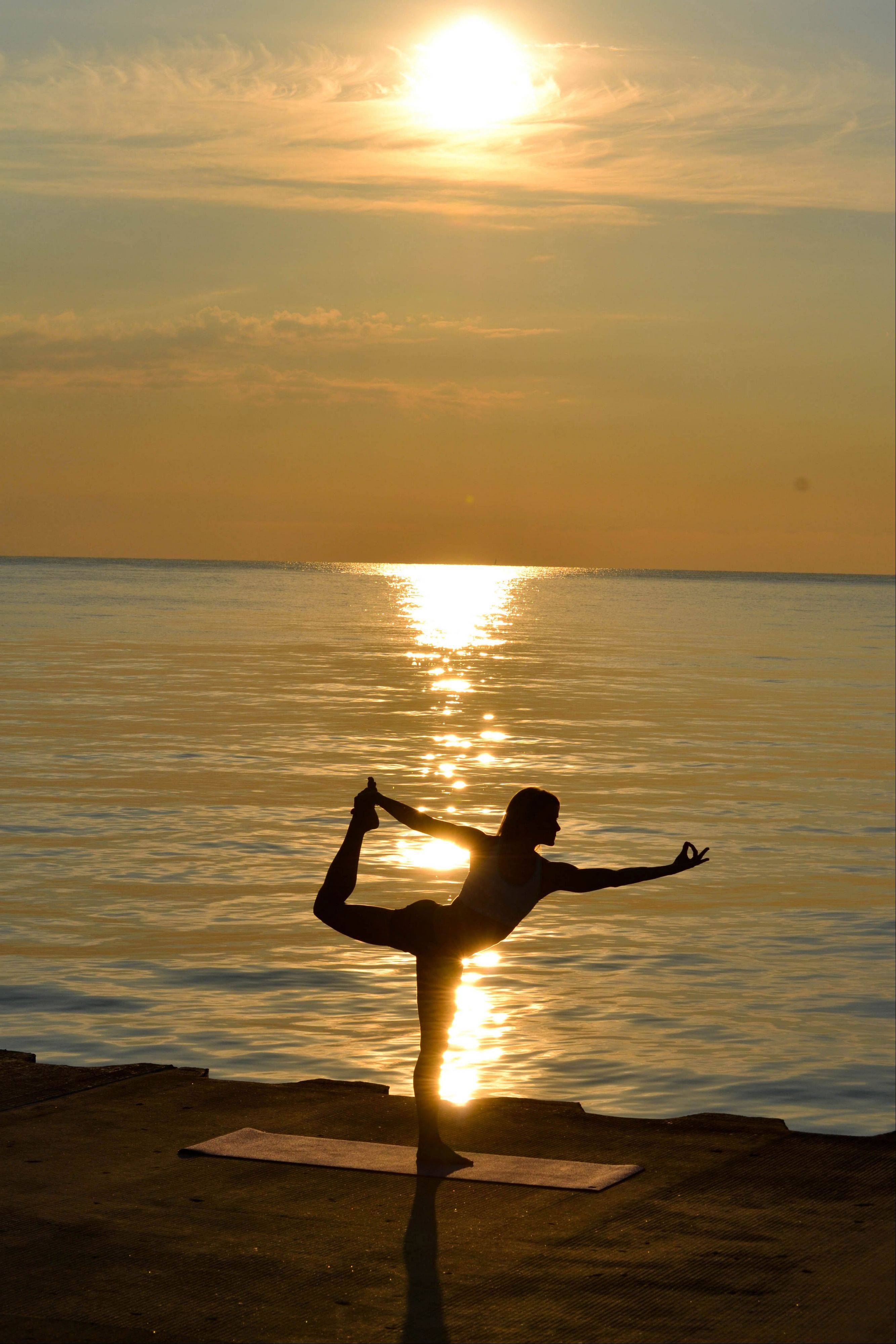 A woman practices yoga during sunrise at Diversey Harbor in Chicago.
