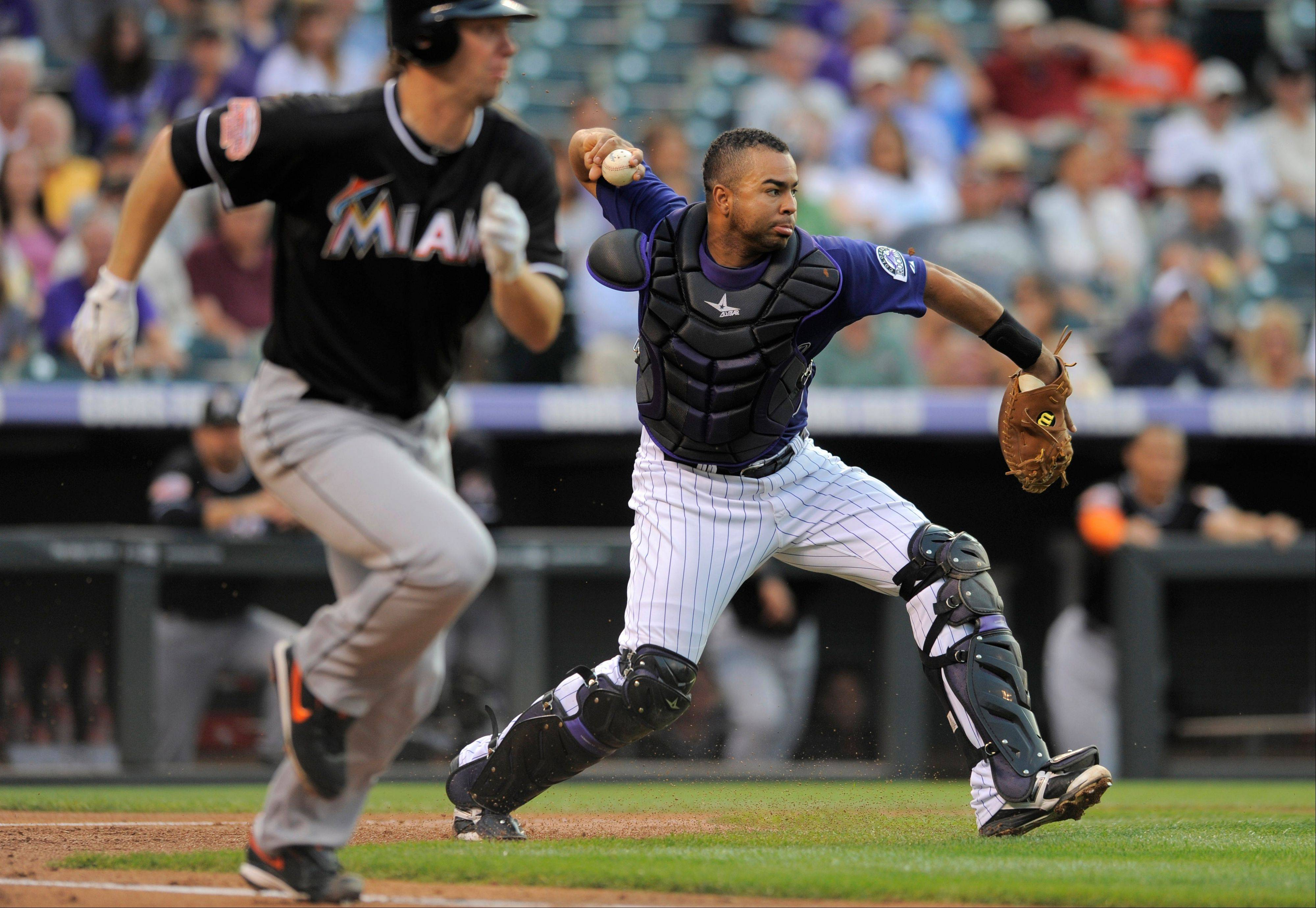 Rockies catcher Wilin Rosario throws too late to get the Marlins' John Buck at second base on a Wade LeBlanc bunt during the second inning Friday in Denver.