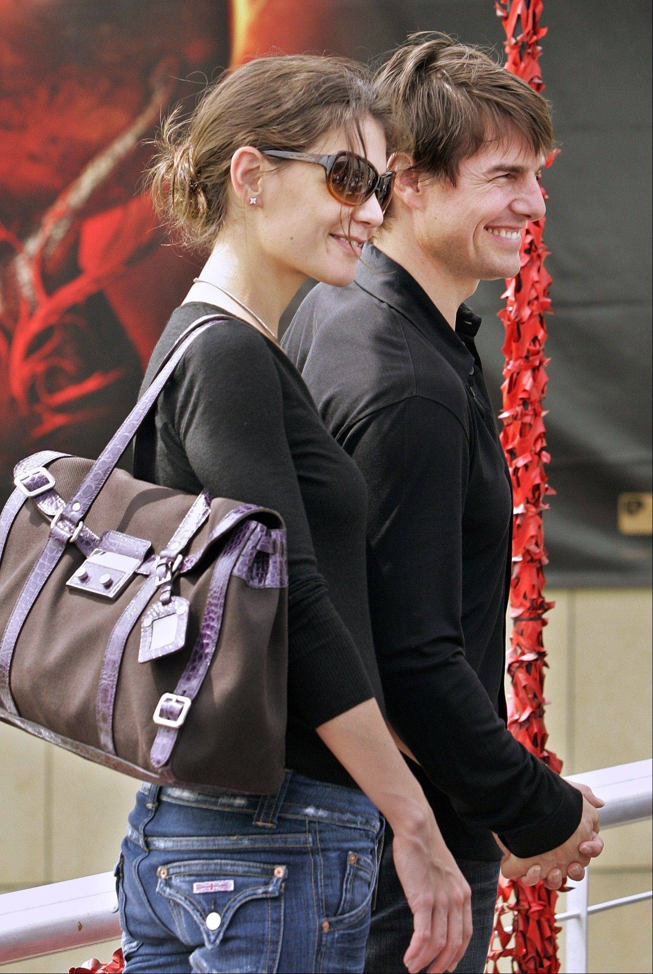 In this June 21, 2005 file photo Katie Holmes sports a Hermes handbag as she and Tom Cruise pose for photographers in Madrid shortly after announcing their engagement. The status handbag market is driven by celebrity trendsetters such as Holmes and Victoria Beckham and now some big auction houses are getting in on the act. They say it's a new and growing category that's attracting sellers and buyers from around the world.