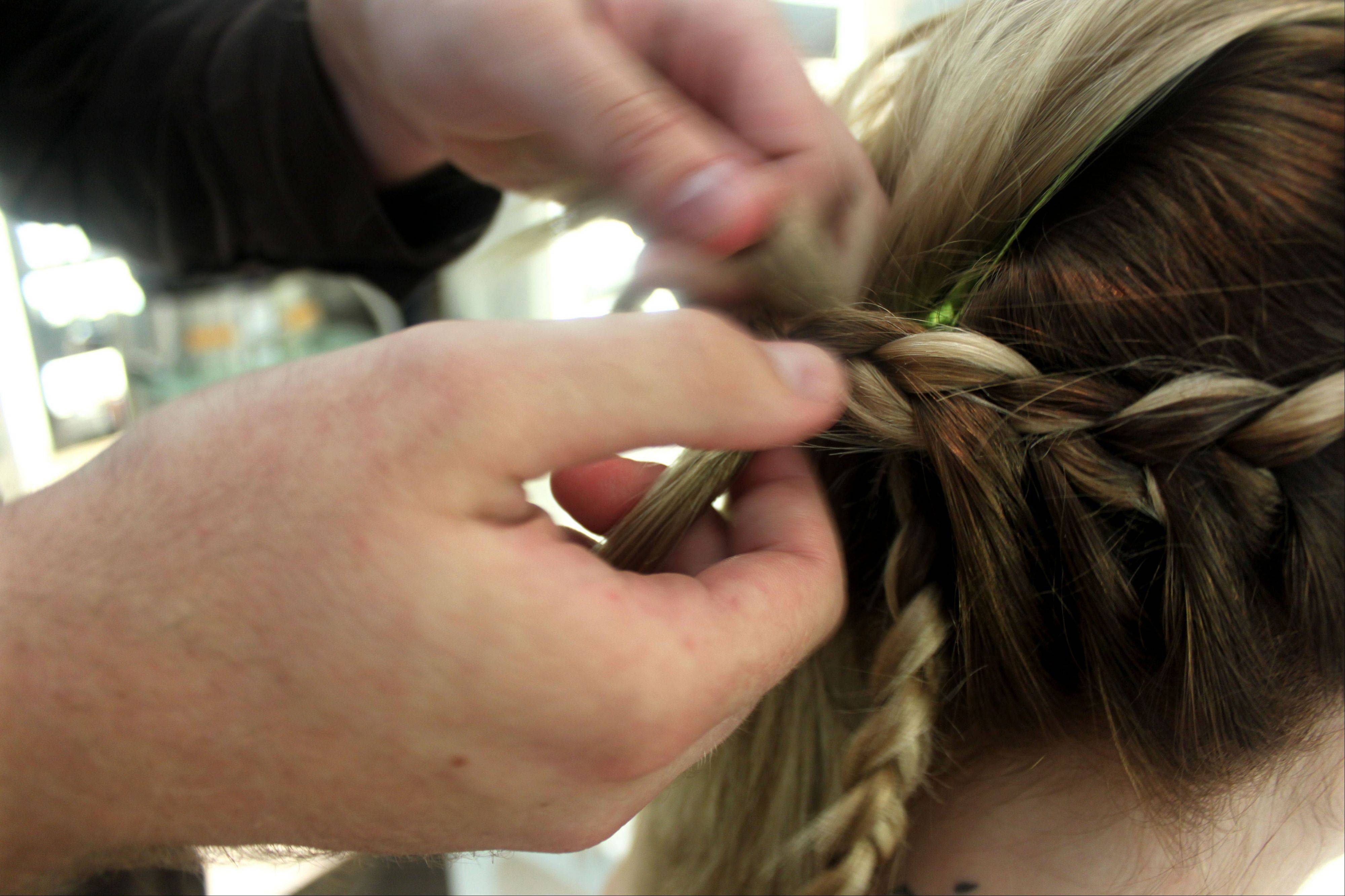 "Stylist Cliff Freeman braids the hair of Danielle Maddox, 25, at Maxine salon's Braid Bar in Chicago on Aug. 1. Salons from Los Angeles to New York are opening ""braid bars,"" offering special menus of different braid styles for a fixed price."