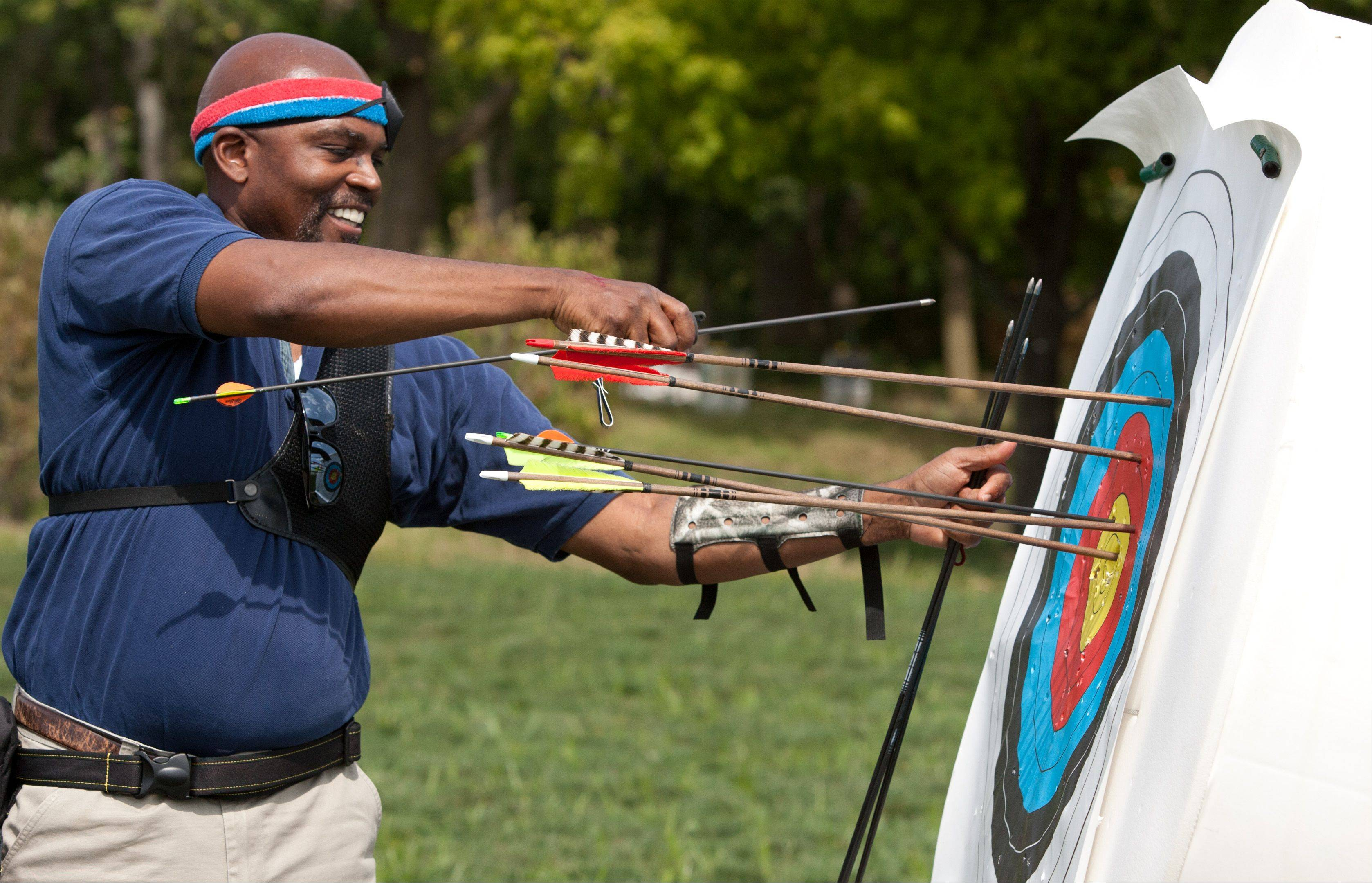 Daniel White/dwhite@dailyherald.com Priest Walker of Wheaton retrieves his arrows during the DuPage County Forest Preserve's opening of an upgraded archery range at the Blackwell Forest Preserve.
