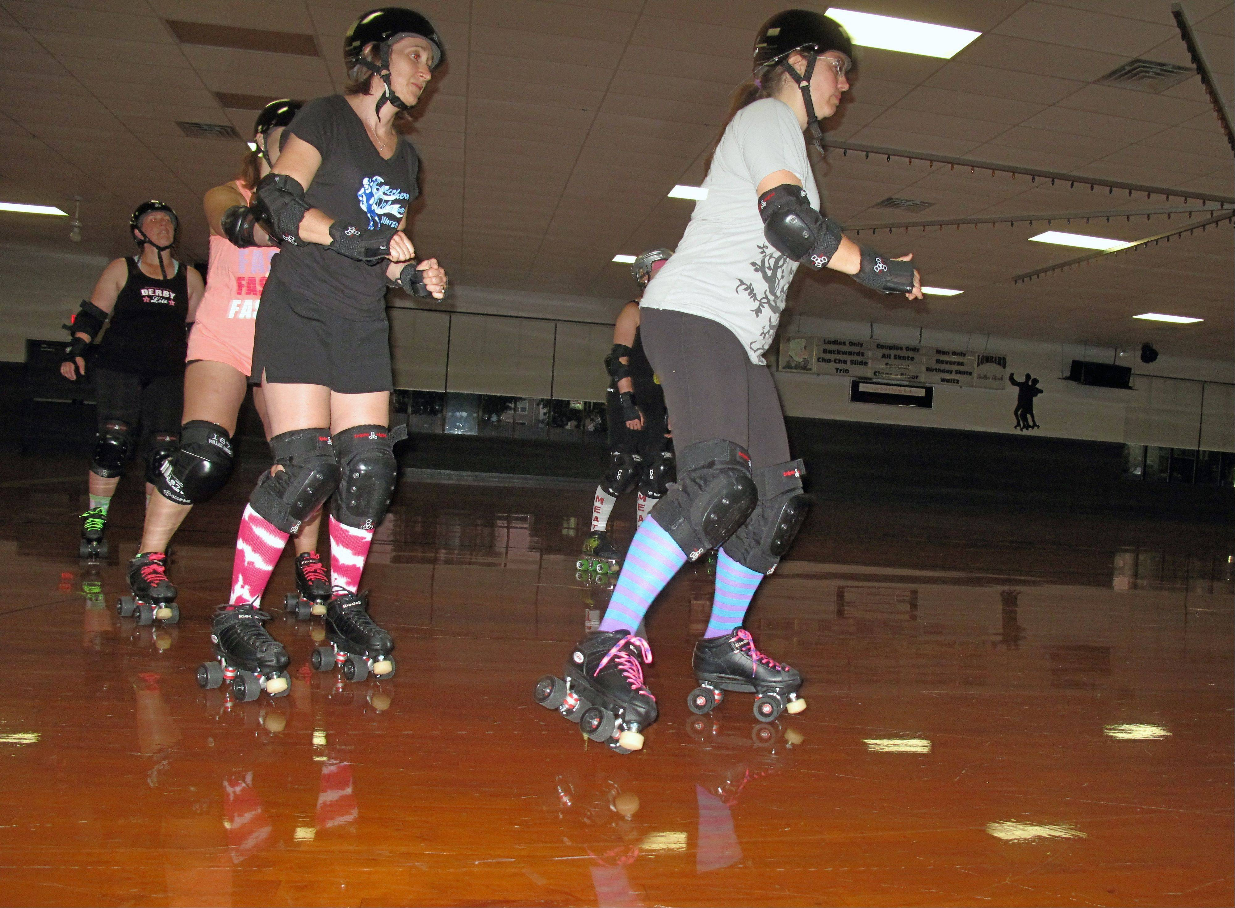 Derby Lite participants Meg Dudek of Frankfort and Melissa Monroe of Mokena lead a line of skaters during a recent fitness class. Derby Lite classes use the drills of classic women's roller derby — without the body-slamming contact — as the foundation for a workout.