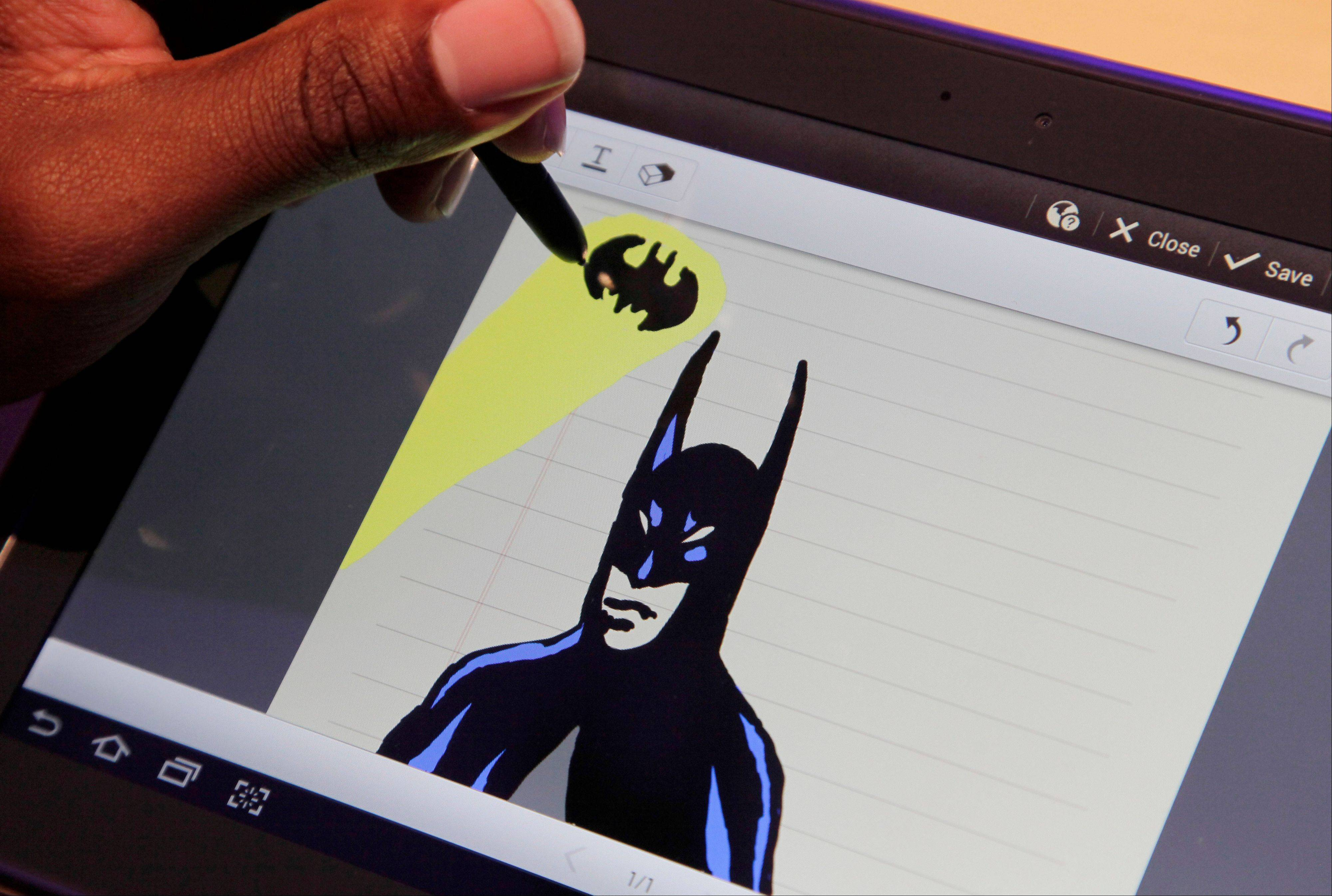 An artist uses the Samsung Galaxy Note to draw a Batman figure Wednesday at a news conference in New York.