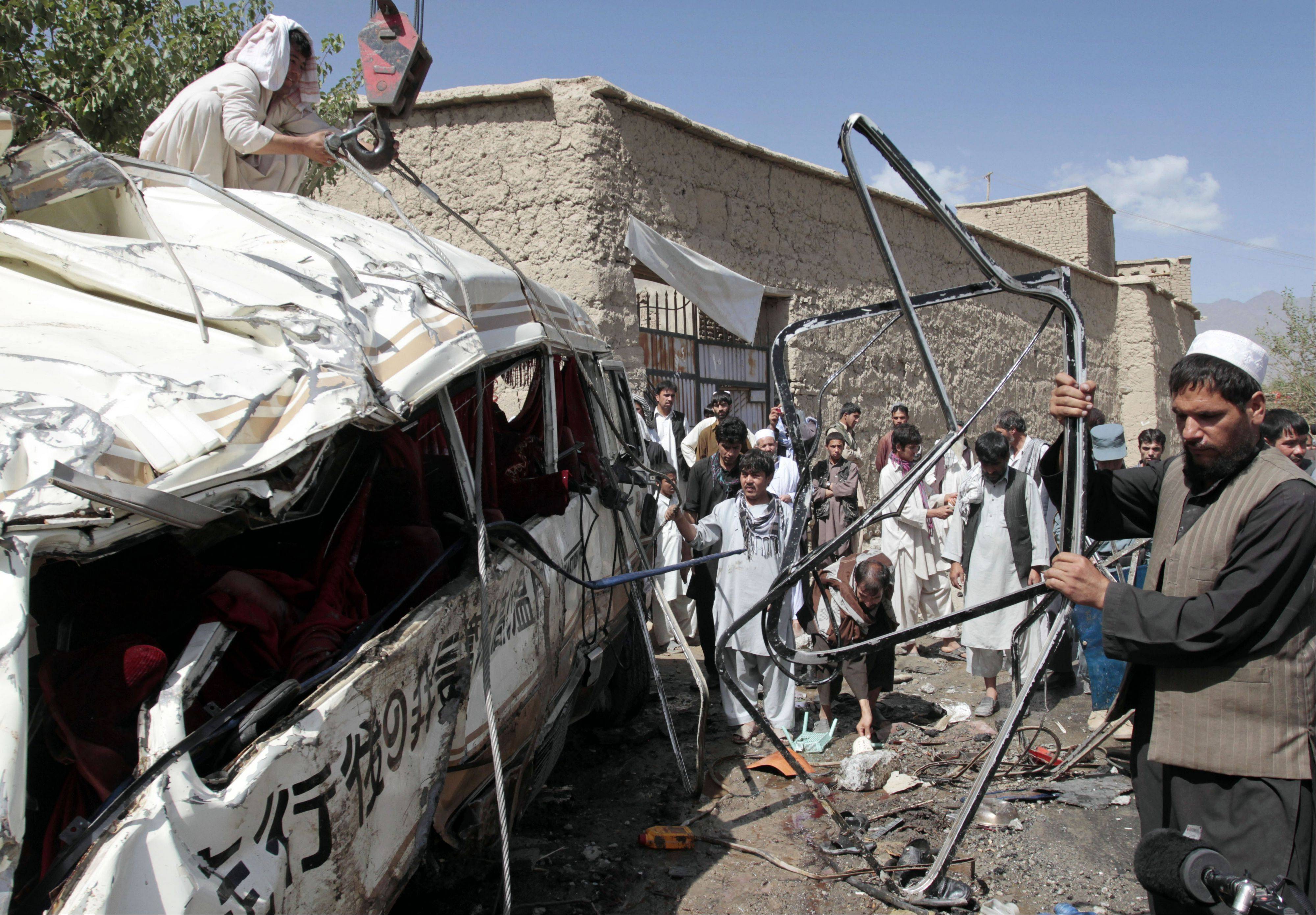 Associated Press/Aug. 7, 2012Men collect parts of a damaged bus, which was hit by a remote control bomb on the outskirts of Kabul, Afghanistan.