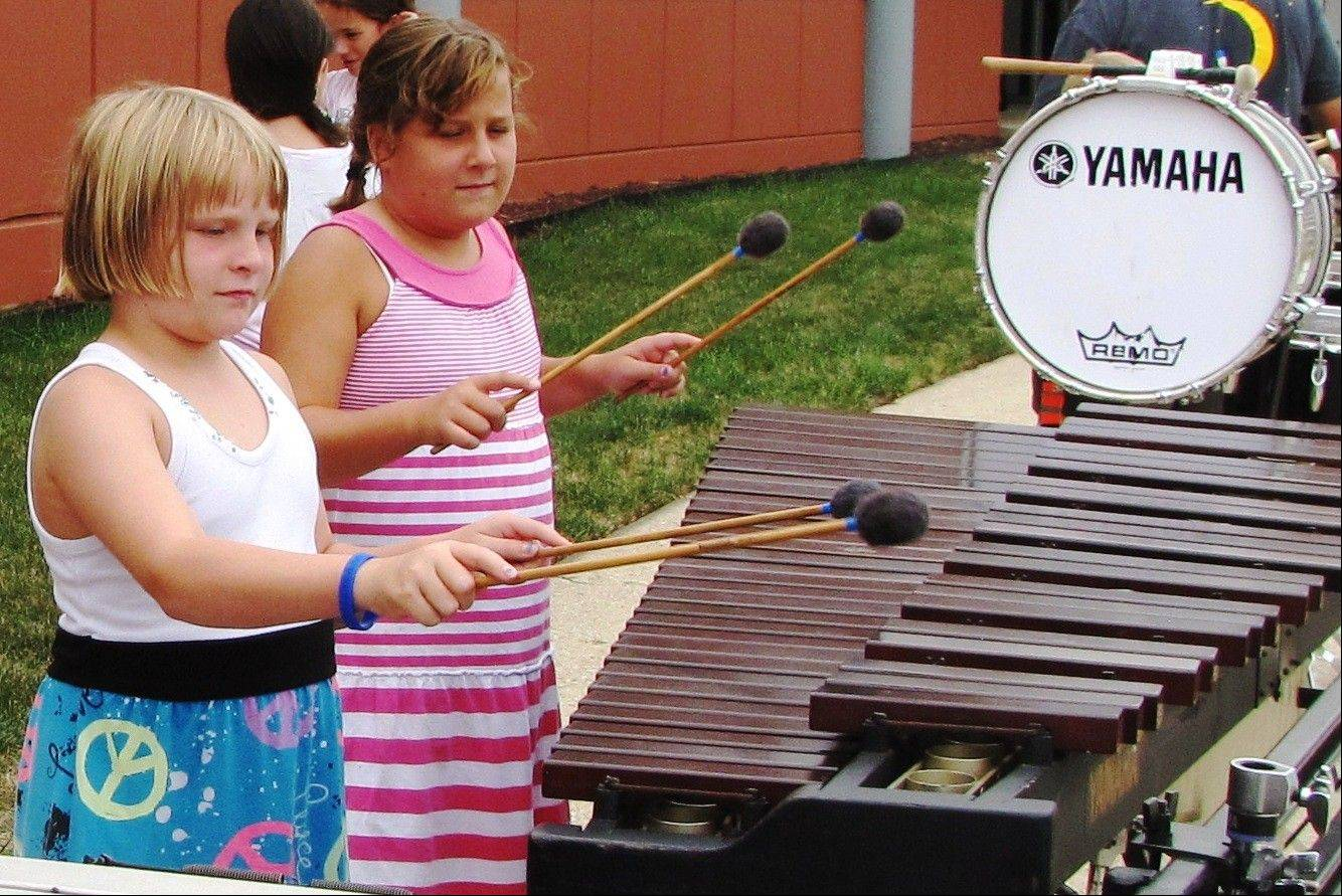 "Twin sisters Genevieve and Claudine Bellot, 9, of Des Plaines enjoy the music they make on a marimba in the ""instrument petting zoo."""