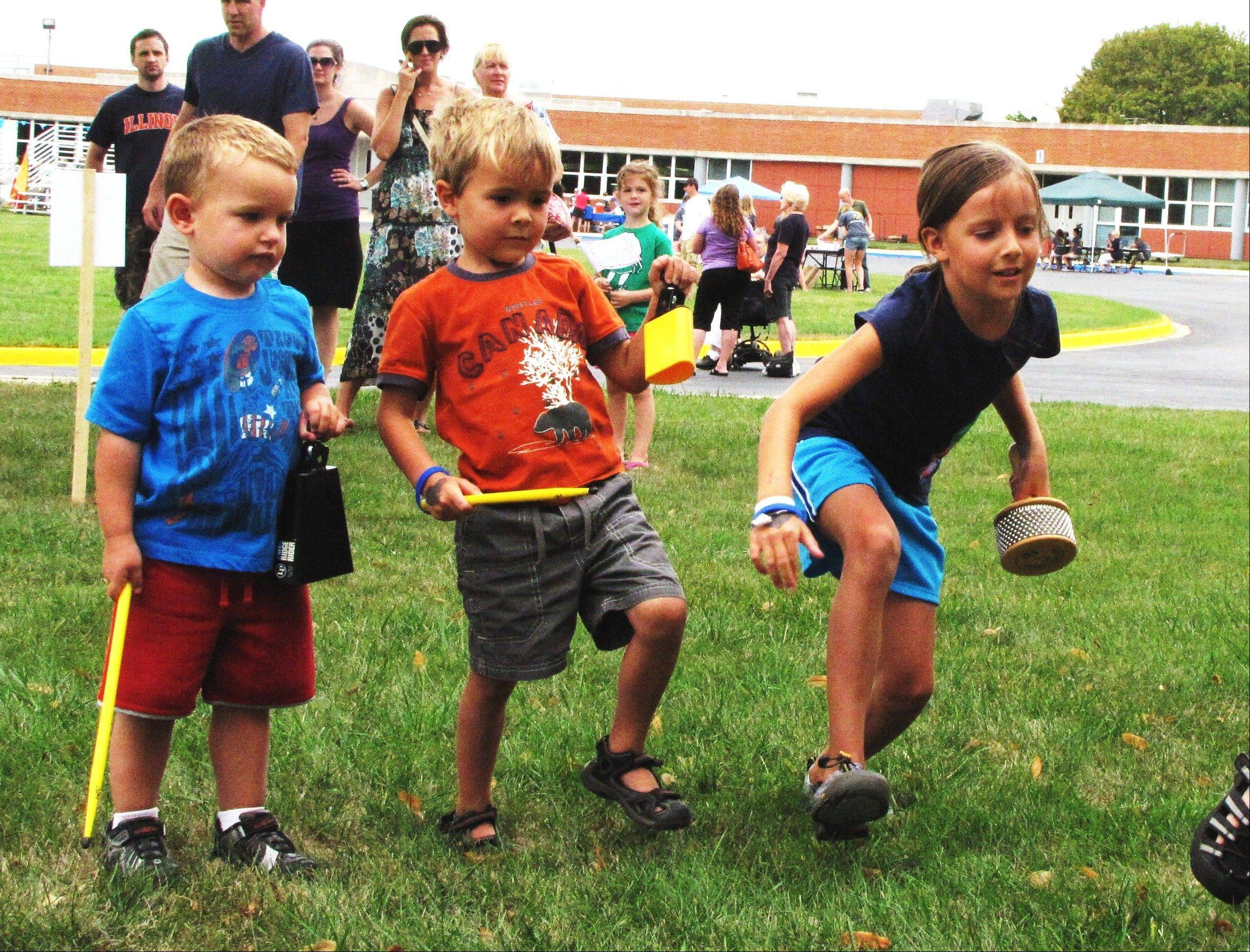 "Joe Buttitta, 3, and Grant, 4, and Alison Biewenga, 8, all of Arlington Heights, compete in a game of percussion ""Simon Plays."""