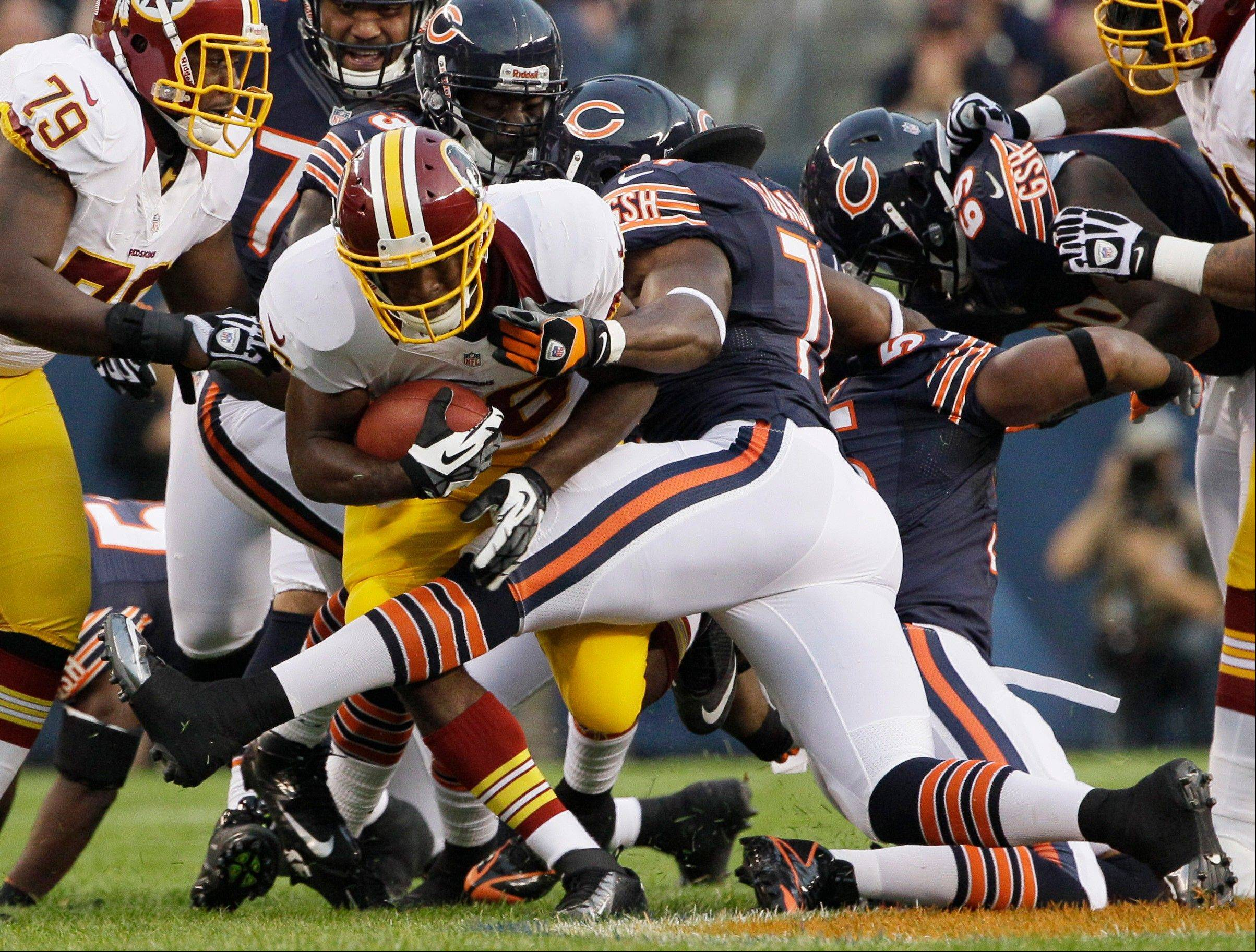 Washington Redskins running back Alfred Morris is tackled by Bears defensive end Israel Idonije Saturday during the first half at Soldier Field.