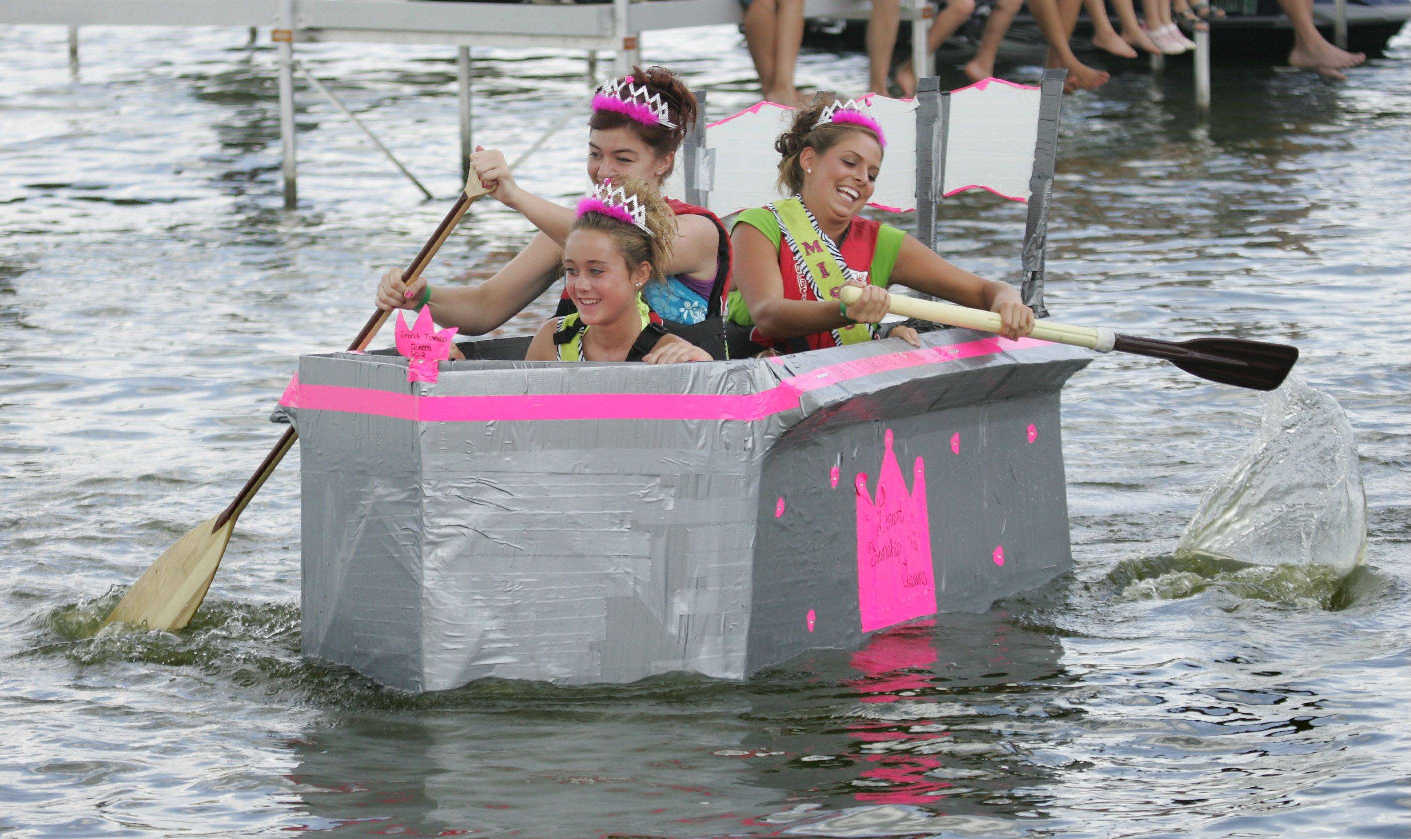 Grant Township queens Junior Miss Gabriela Schoenberg, front, Teen Miss Jessie Burdett, and Miss Bethani Jacobsen paddle their boat along the racecourse during the annual Cardboard Cup Regatta Sunday at Lakefront Park sponsored by the Village of Fox Lake Parks and Recreation Department. Contestants built boats made strictly of cardboard, duct tape and paint and raced for medals and trophies.