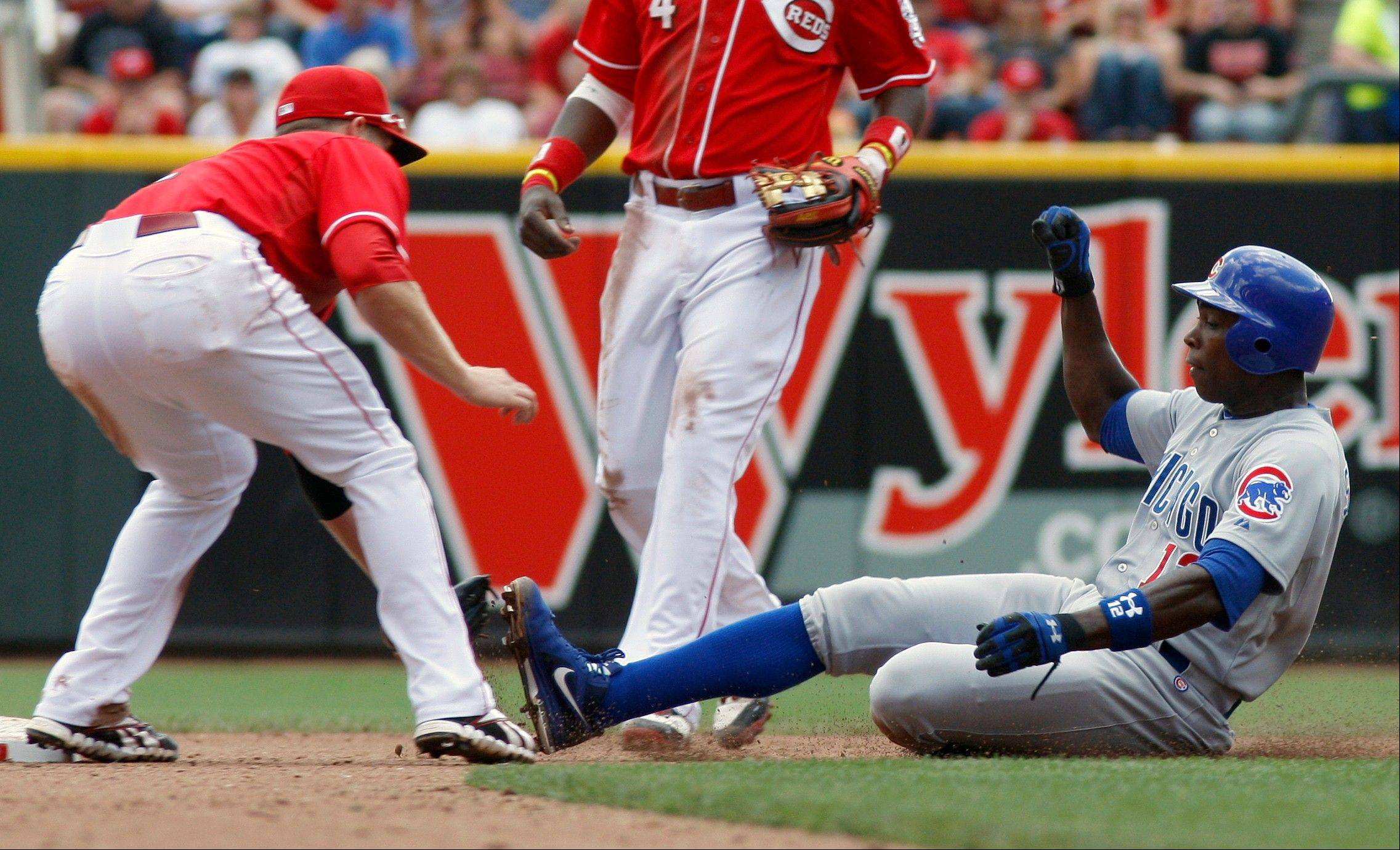 Cubs outfielder Alfonso Soriano, right, is tagged out by Cincinnati Reds shortstop Zack Cozart, left, after being caught stealing second base in Sunday's fourth inning in Cincinnati.