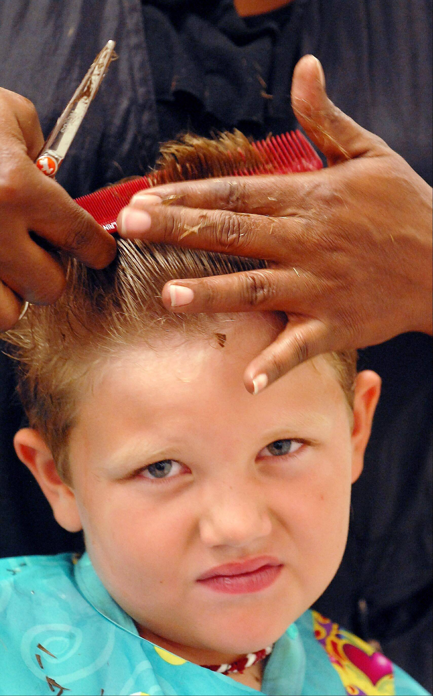 Wesley Brooks, 7, of Huntsville, Ala., has his hair cut by Melinda Gilbert at the J.C. Penney styling salon in Huntsville, Ala. J.C. Penney is running a nationwide program giving kids ages 5-12 free back-to-school haircuts during the month of August.