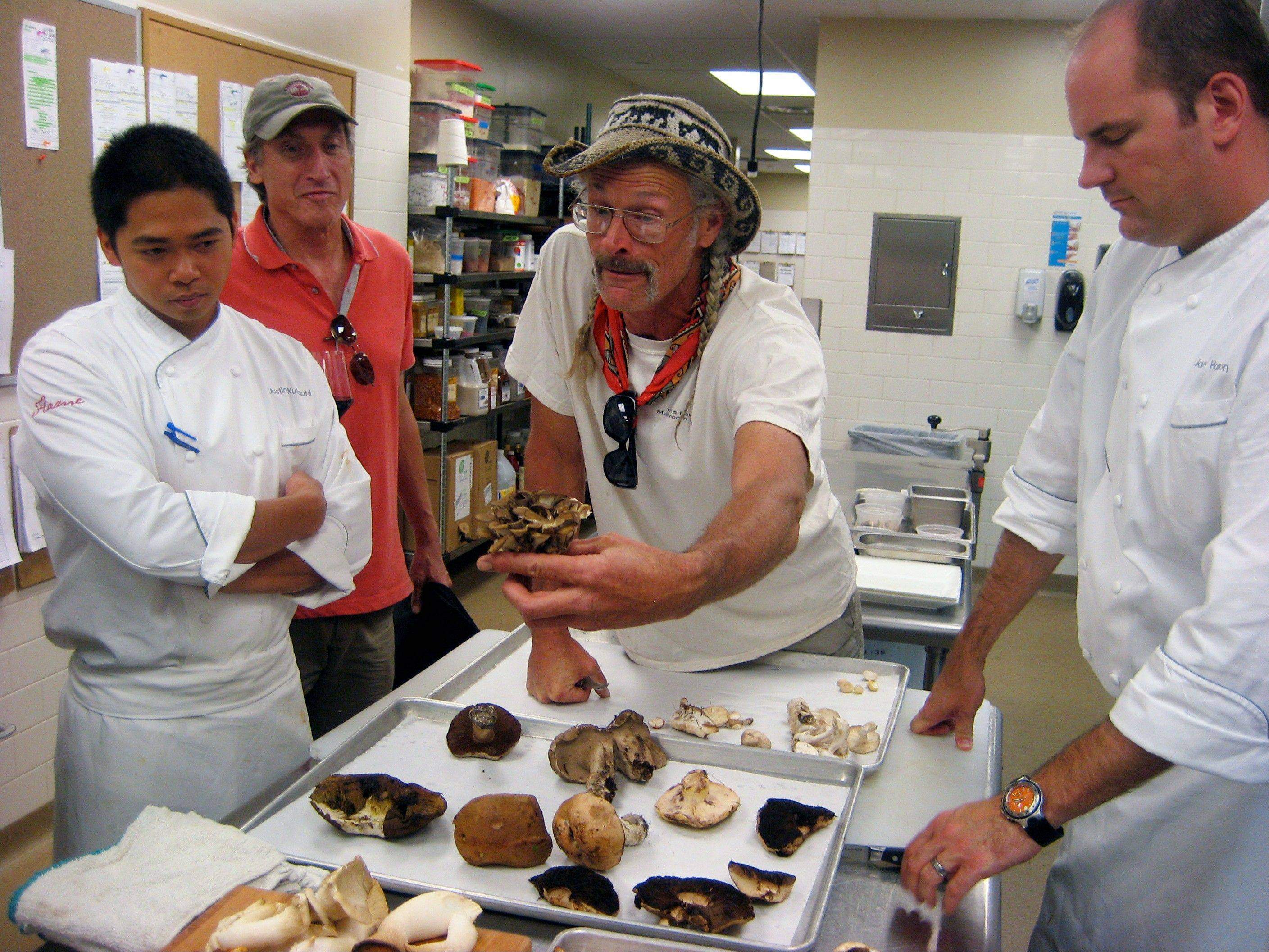 This Aug. 4, 2012 photo shows Four Seasons Resort Vail Executive Chef Jason Harrison, left, looking on as mushroom guide Larry Evans, center, shows off specimens collected during a foraging trip organized by Four Seasons Resort Vail in Vail, Colo. For $200 a person, the Four Seasons Resort Vail is sending out guided expeditions in luxury SUVs to look for mushrooms. The Mushrooms & Mercedes program includes a lunchtime break with wine, cheese and prosciutto, and ends with a three-course mushroom-themed meal back at the hotel.
