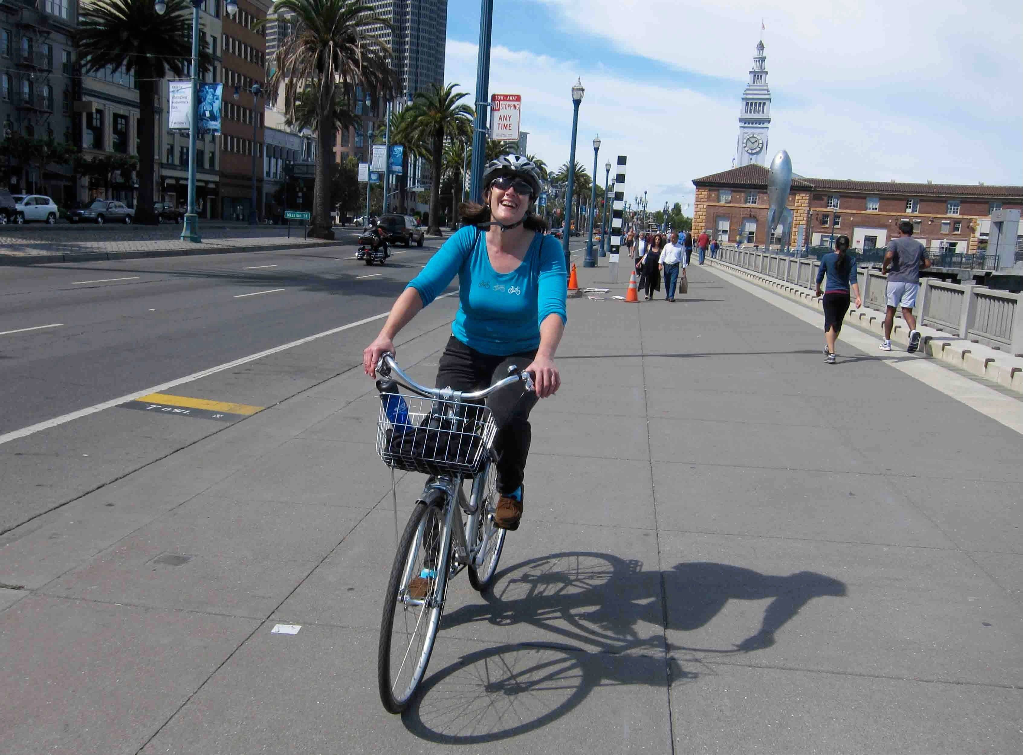 Paula Froke, of New York, rides along the Embarcadero in San Francisco during a Streets of San Francisco bike tour.