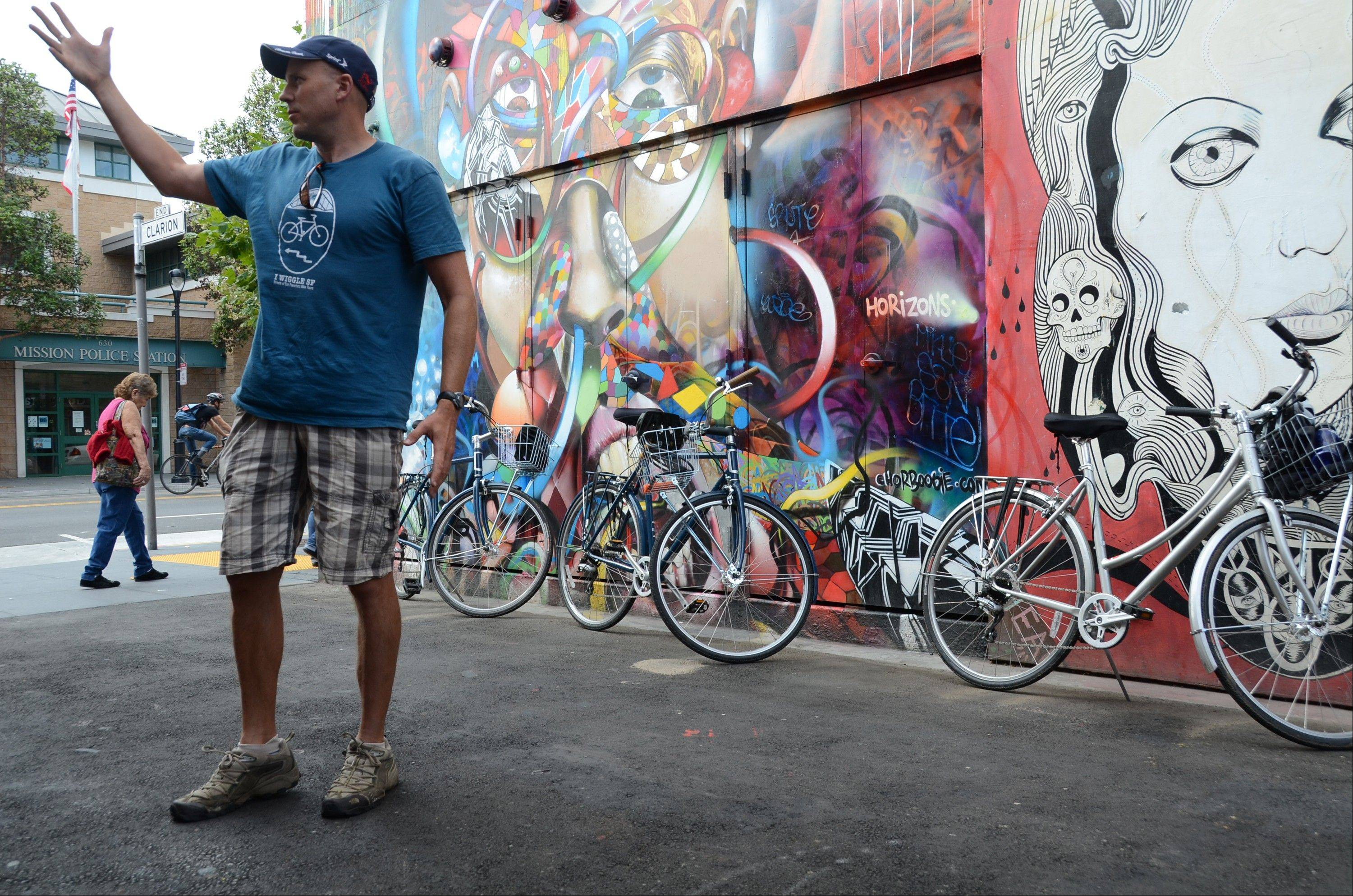 Streets of San Francisco Bike Tours guide and co-founder Eoin Canny explains the history of mural art in the Mission District during a tour in San Francisco.