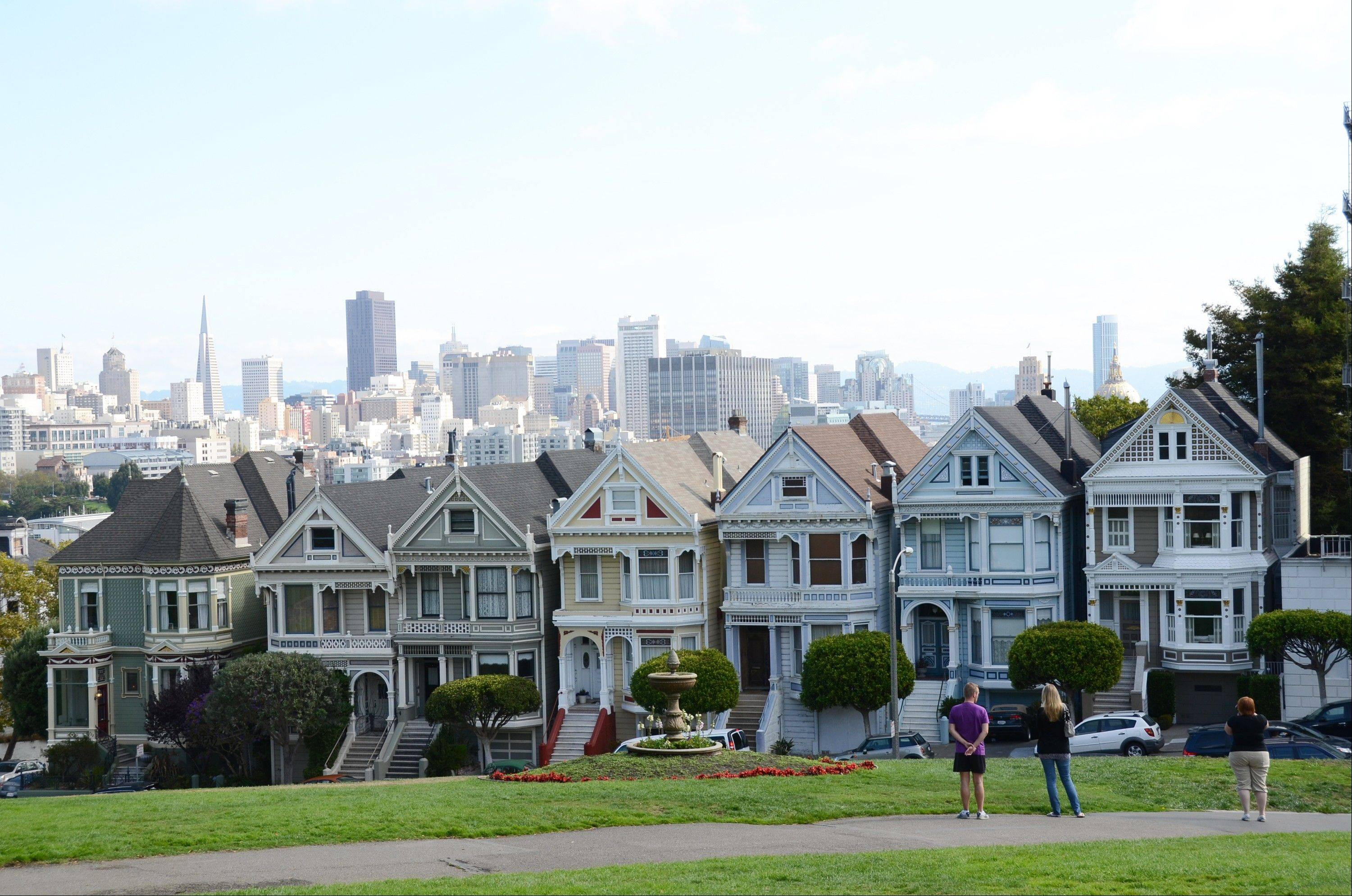 "An escalating row of Victorian houses known as ""Painted Ladies"" on the edge of Alamo Square Park, overlook the San Francisco skyline at the start of a Streets of San Francisco bike tour."