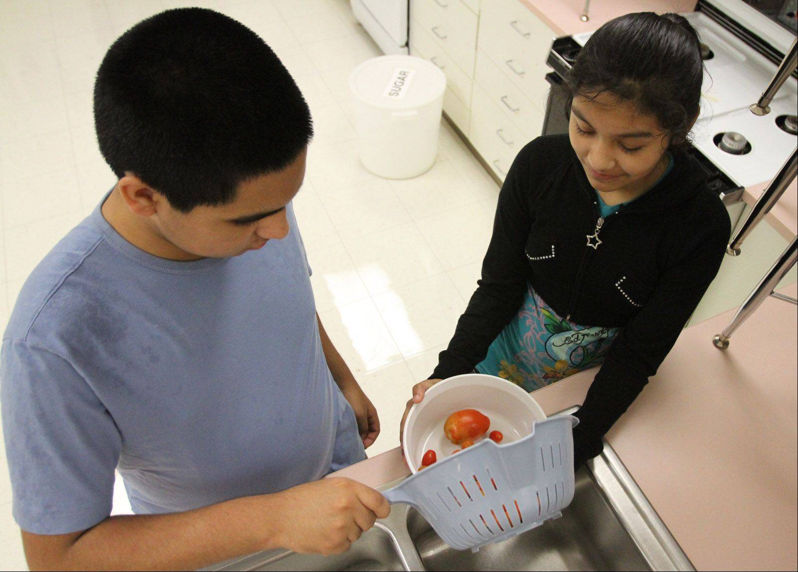 Students Luis Rodriguez and Alondra Ramos, both eighth-graders at London Middle School, wash tomatoes recently picked out of the school garden.