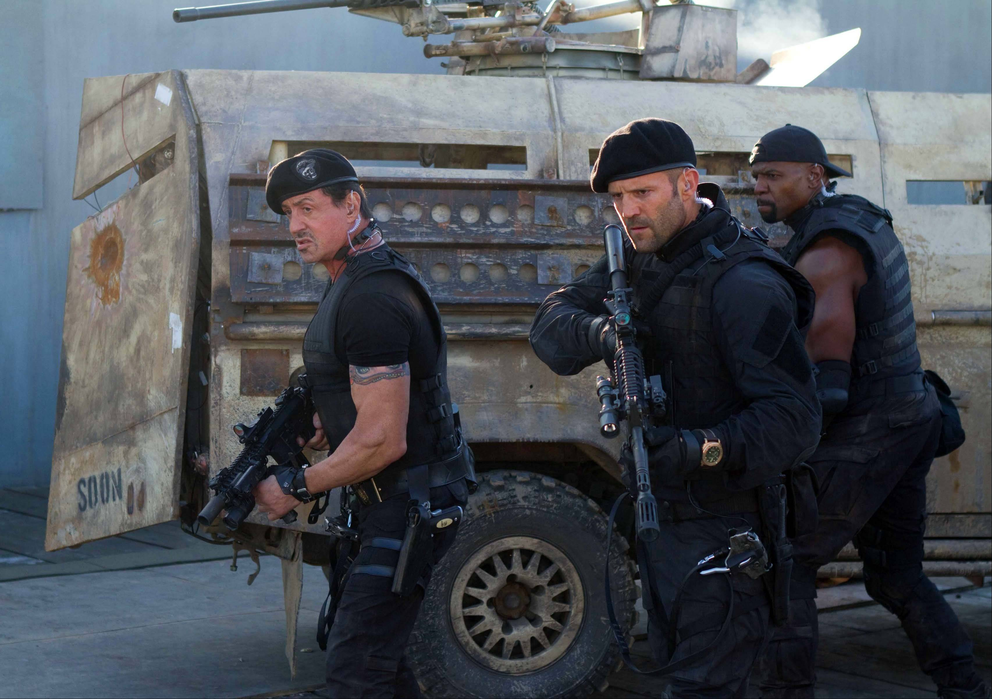 "From left, Sylvester Stallone, Jason Statham and Terry Crews in a scene from ""The Expendables 2,"" which raked in $28.2 million, down from the $34.8 million the first film made in its first weekend of release."