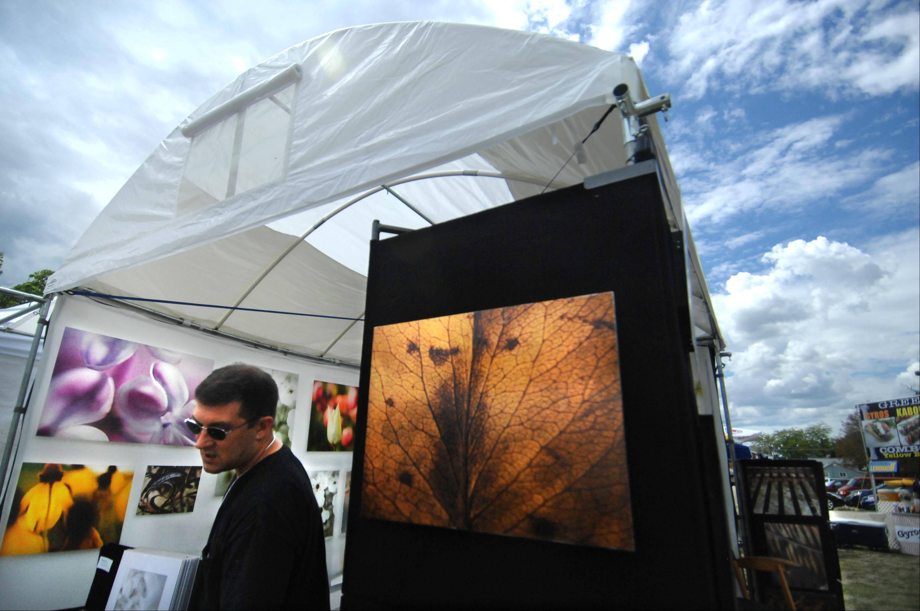 Fine art photographer John Granata, of Lily Lake, shows browsers his work Sunday during the Huntley Artfest. He won Best of Show for his booth.