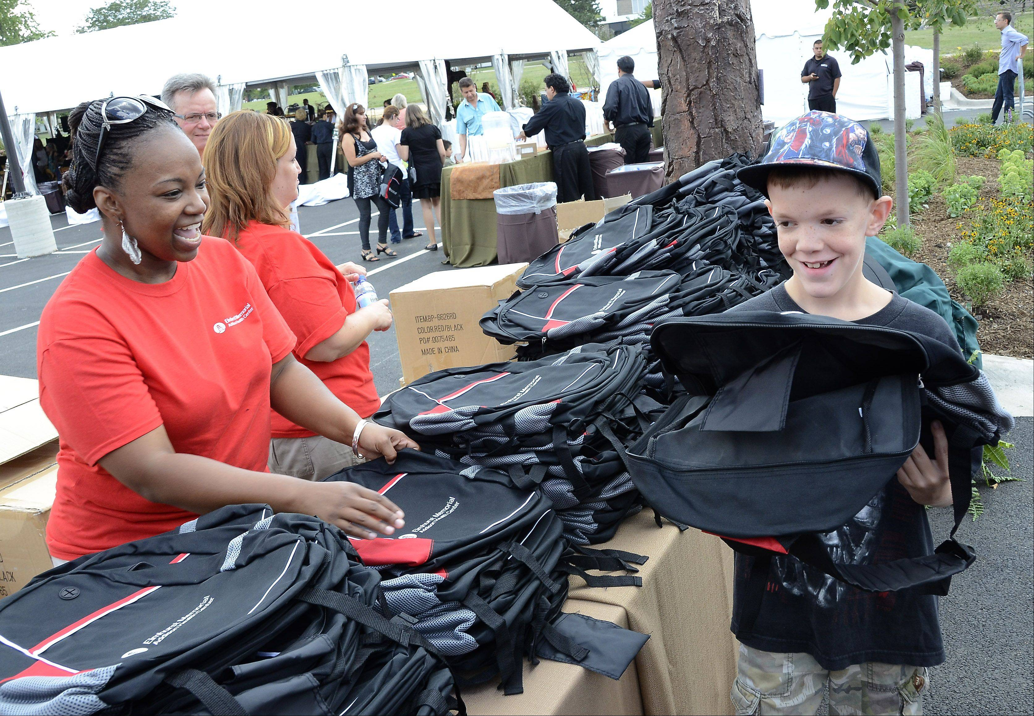 Carematch counselor Latoiya Christian, of Lombard, and John Joseph, 9, of Itasca, both wear big smiles after she gave him a backpack at the opening of the Elmhurst Memorial Hospital Addison Health Center Sunday afternoon in Addison.