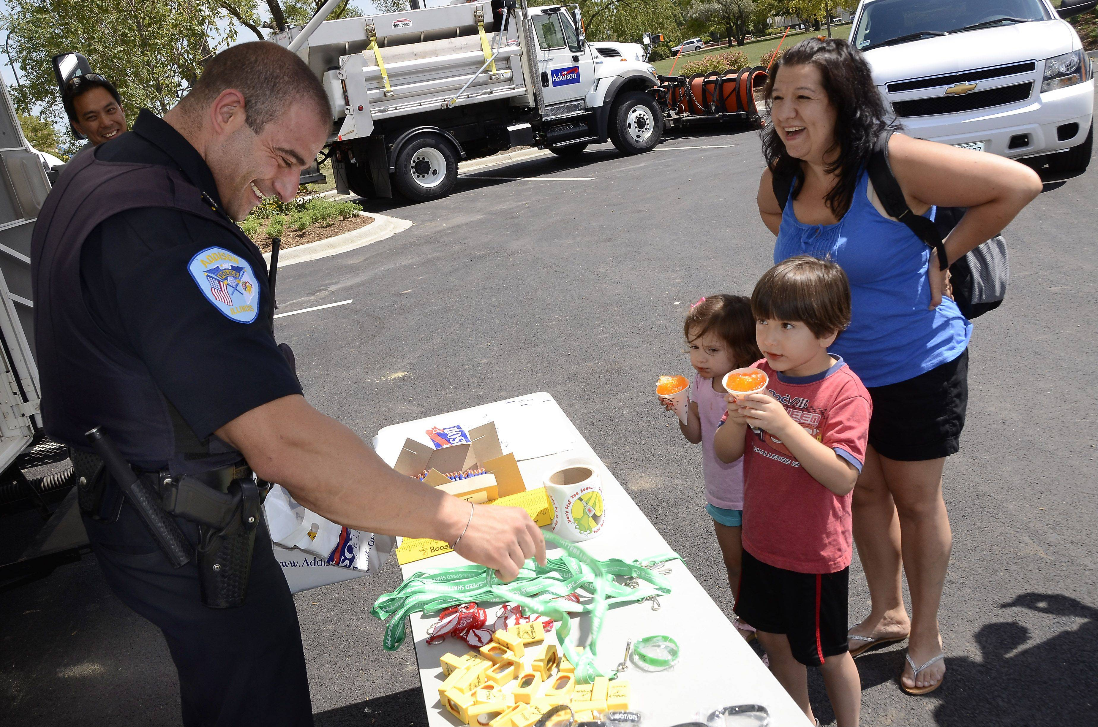 Addison police patrolman Joe Merendino gathers some souvenirs for Mina Alliaj, 3, Masimo Alliaj, 4, and Lucy Alliaj of Elmhurst Sunday at the opening of the Elmhurst Memorial Hospital Addison Health Center.