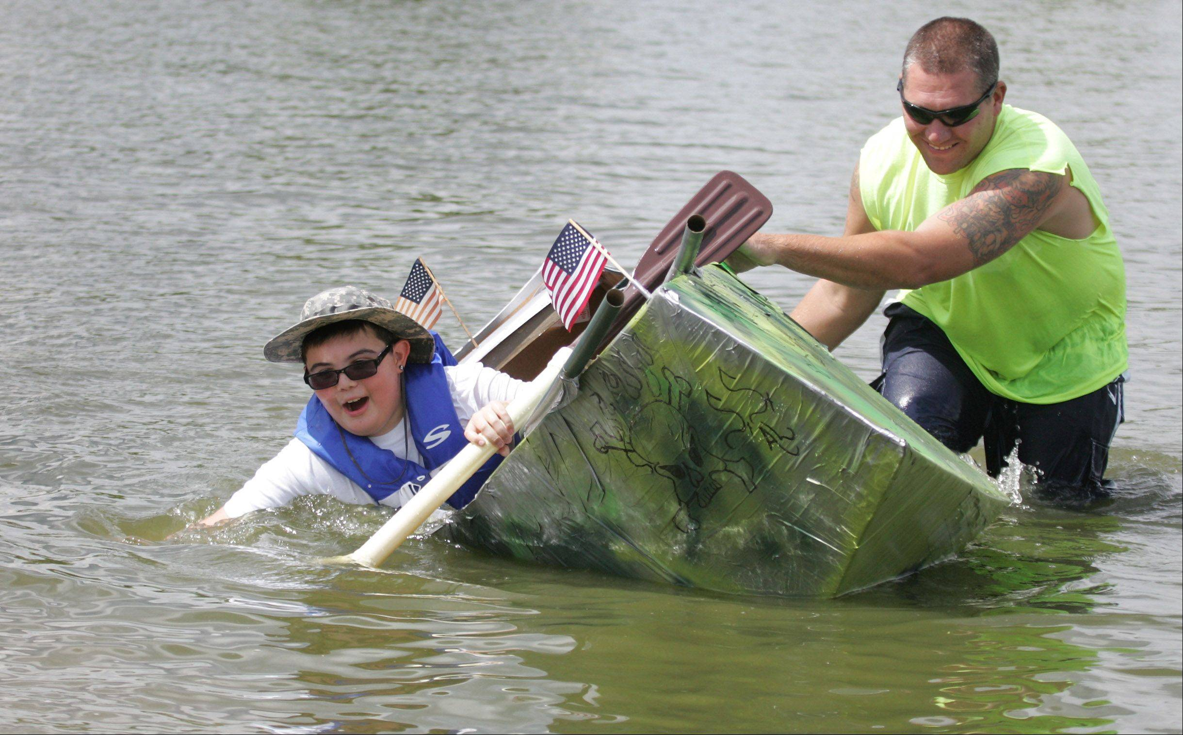 Alex Masterton, 12, quickly sinks in his boat as Fox Lake firefighter Dana Magness tries to help during the annual Cardboard Cup Regatta Sunday at Lakefront Park sponsored by the Village of Fox Lake Parks and Recreation Department. Contestants built boats made strictly of cardboard, duct tape and paint, and then raced them for medals and trophies.