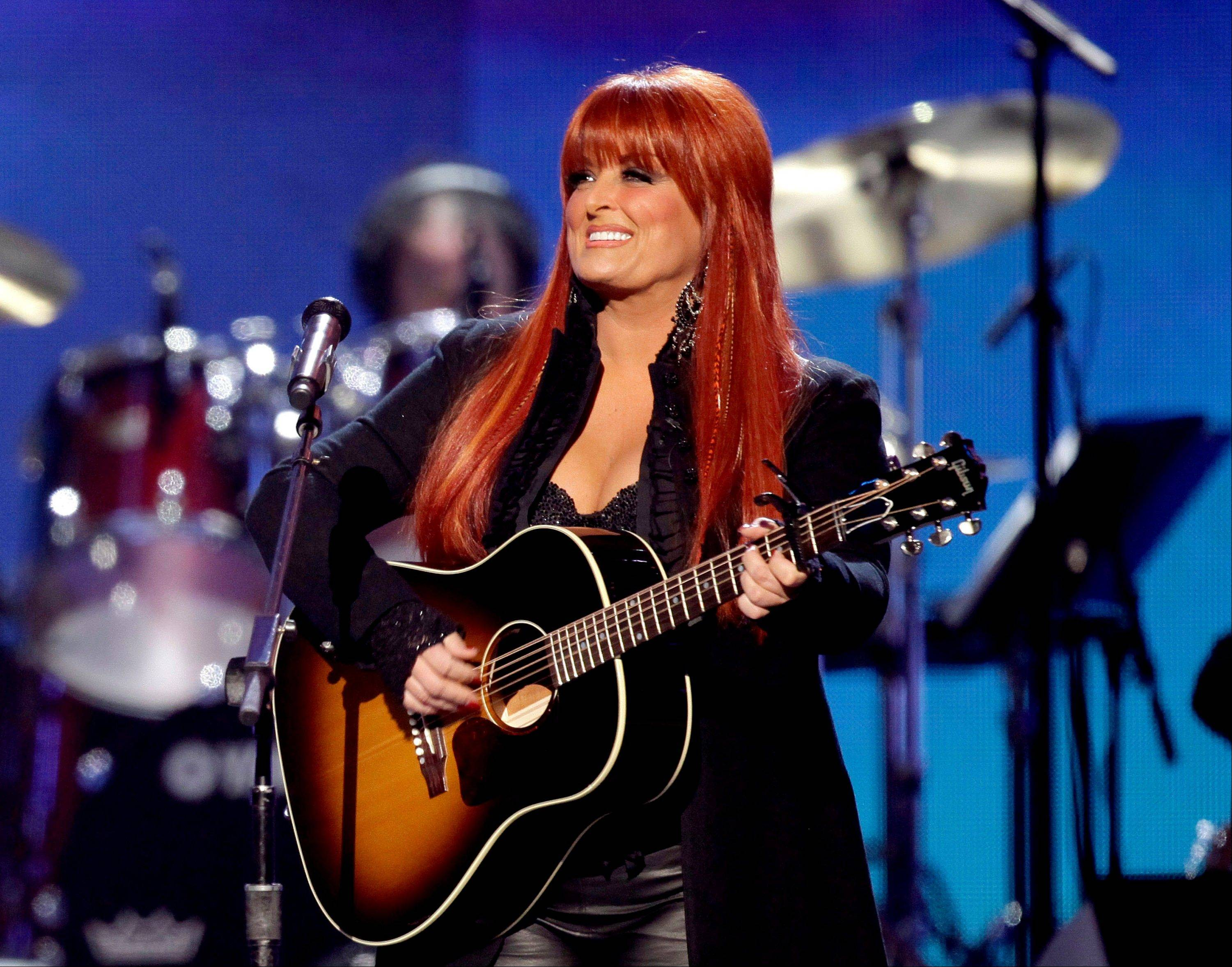 This April 4, 2011 file photo shows country winger Wynonna Judd from The Judds, performing at the Girls' Night Out: Superstar Women of Country in Las Vegas. Judd says she is postponing scheduled concerts in Canada next week after her husband was hurt in a motorcycling accident Saturday in South Dakota.
