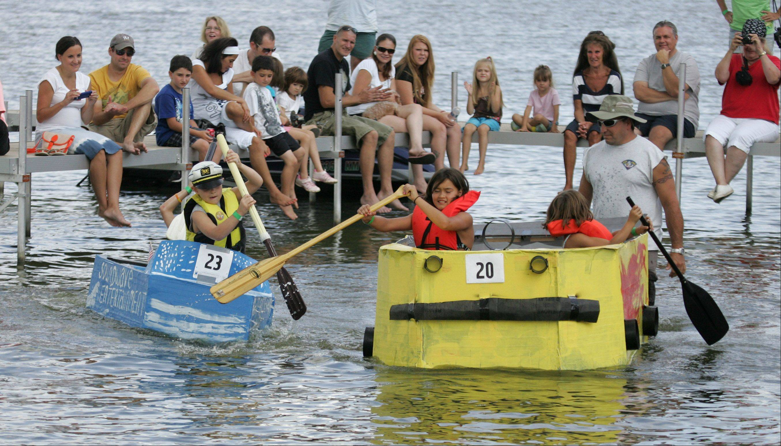 Spectators on the dock watch as the Soundwave Entertainmant boat battles the Yellow Car Boat during the annual Cardboard Cup Regatta Sunday at Lakefront Park sponsored by the Village of Fox Lake Parks and Recreation Department. Contestants built boats made strictly of cardboard, duct tape and paint and raced for medals and trophies.