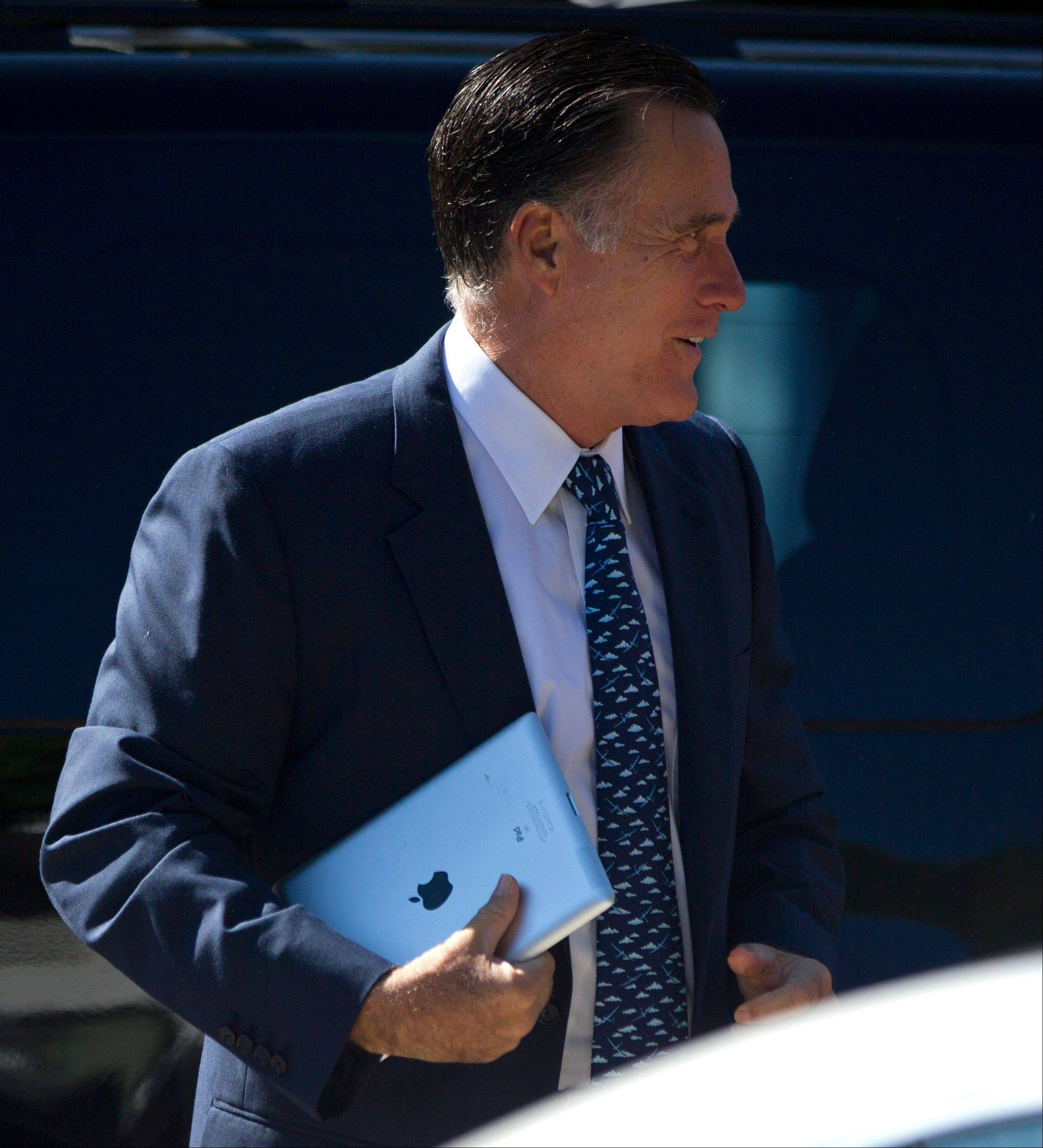 Republican presidential candidate, former Massachusetts Gov. Mitt Romney, carries an iPad as he walks into the Church of Jesus Christ of Latter-day Saints on Sunday in Wolefboro, N.H.