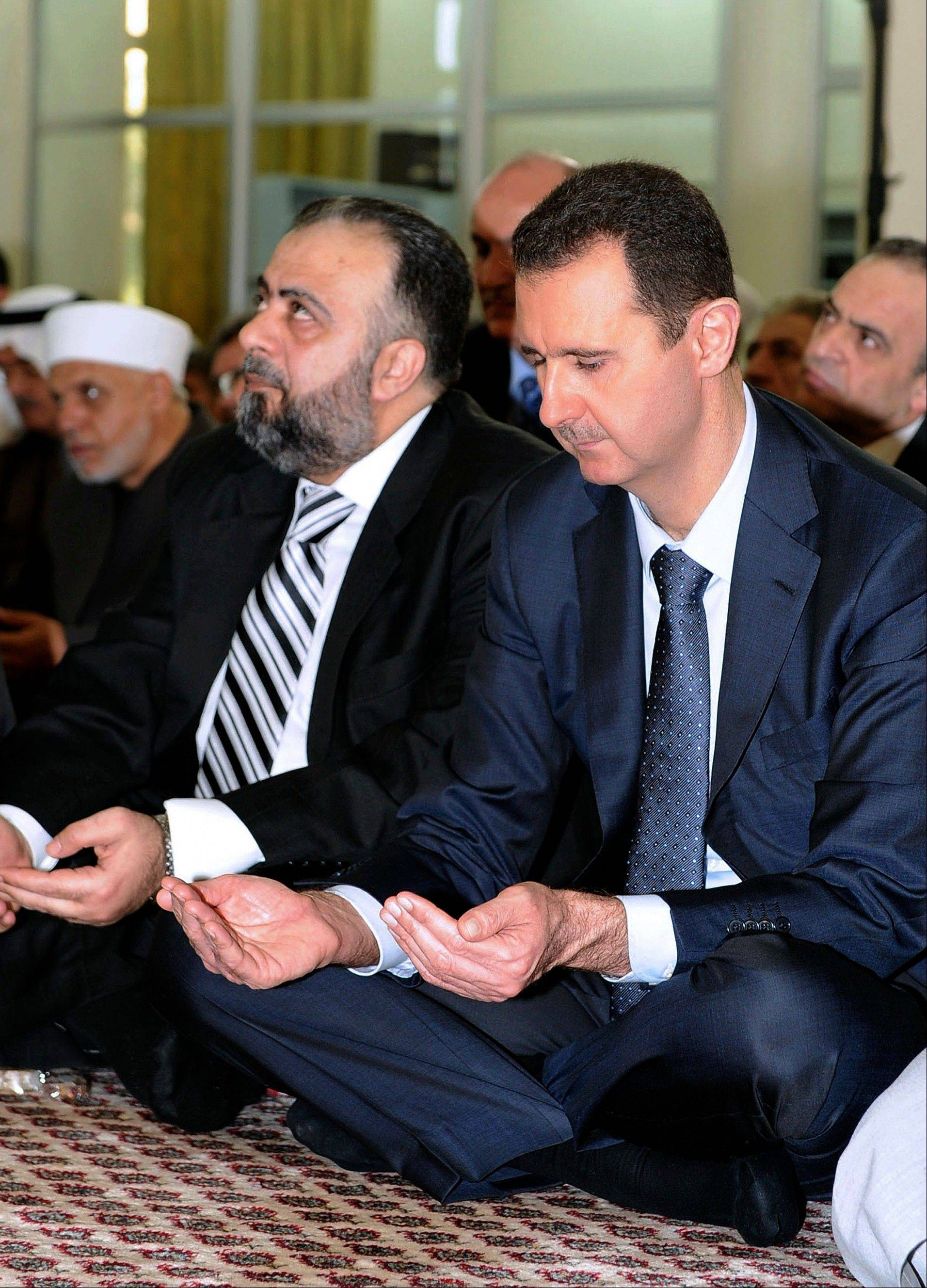 In this photo released by the Syrian official news agency SANA, Syrian president, Bashar Assad, performs Eid prayers in the Hamad Mosque in Damascus, Syria, Sunday. Eid al-Fitr is a three-day holiday marking the end of the holy month of Ramadan. The last time he appeared in public was July 4, when he gave a speech in parliament.