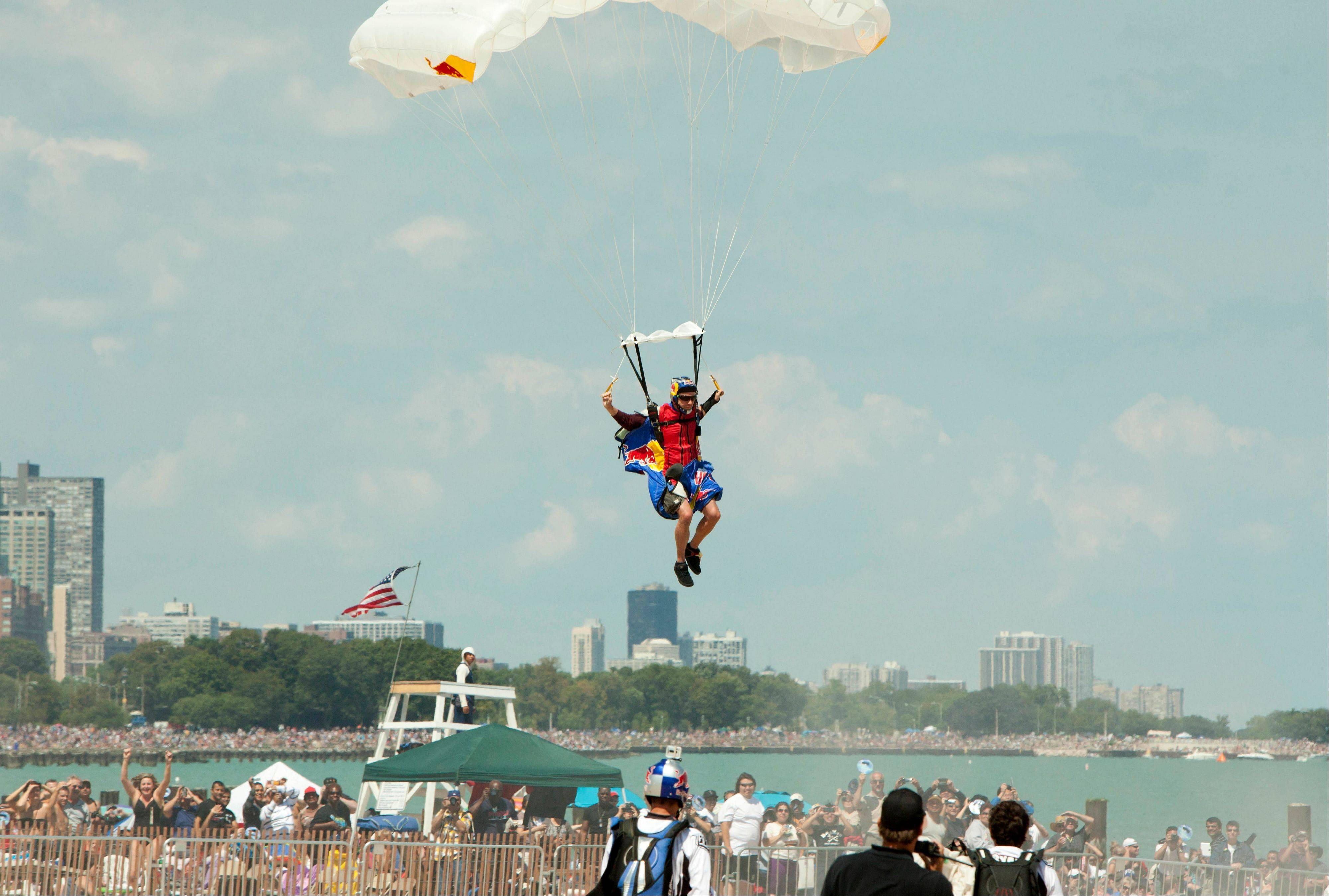 A member of the Red Bull Air Force Team parachutes on to North Beach before a large crowd on the opening day of the Chicago Air and Water Show on Saturday, Aug. 18, 2012 in Chicago.