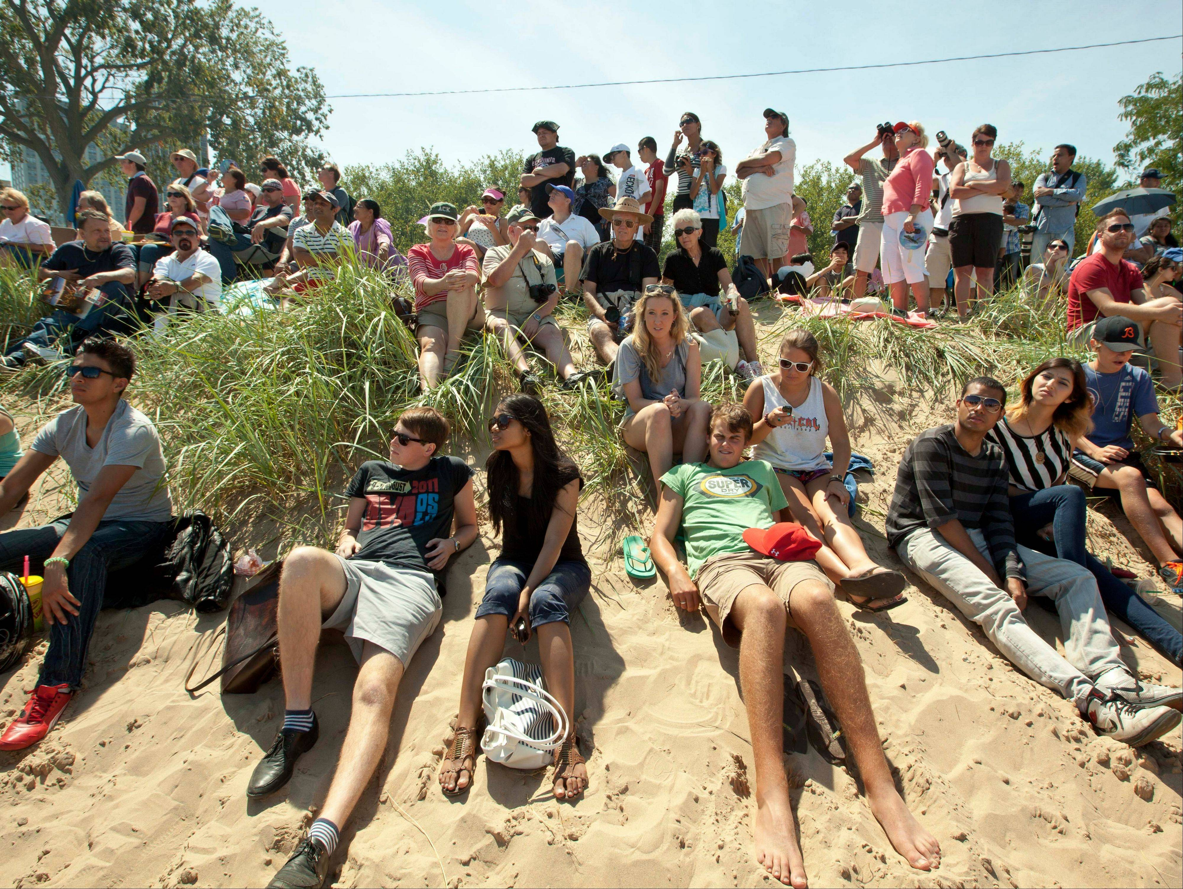 Visitors to the Chicago Air and Water Show position themselves on sand dunes to get a slightly elevated vantage point on Saturday, Aug. 18, 2012 in Chicago.