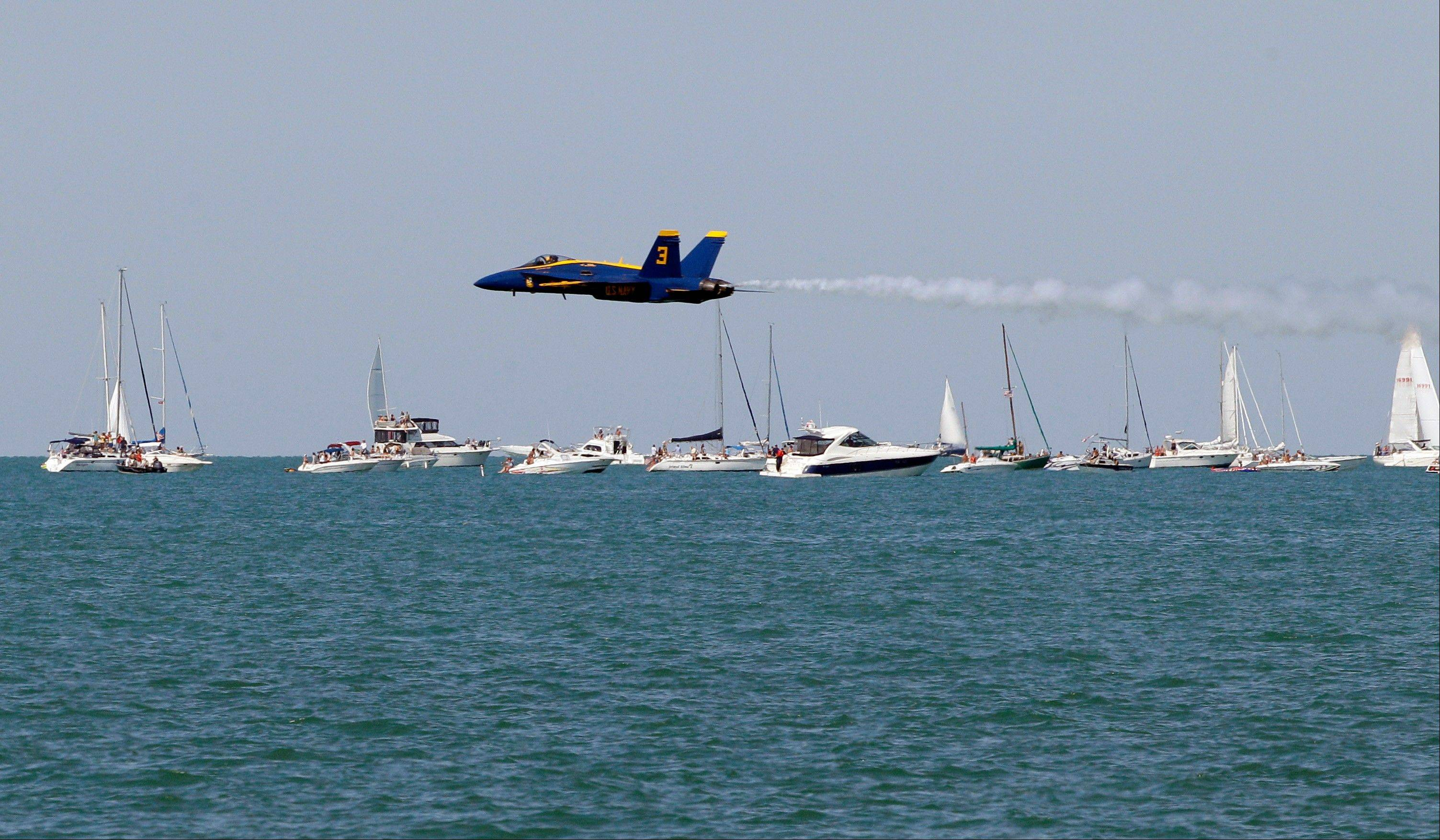 A member of the U.S. Navy Blue Angels makes a low pass over Lake Michigan during the Chicago Air and Water Show on Sunday, Aug. 19, 2012, in Chicago.