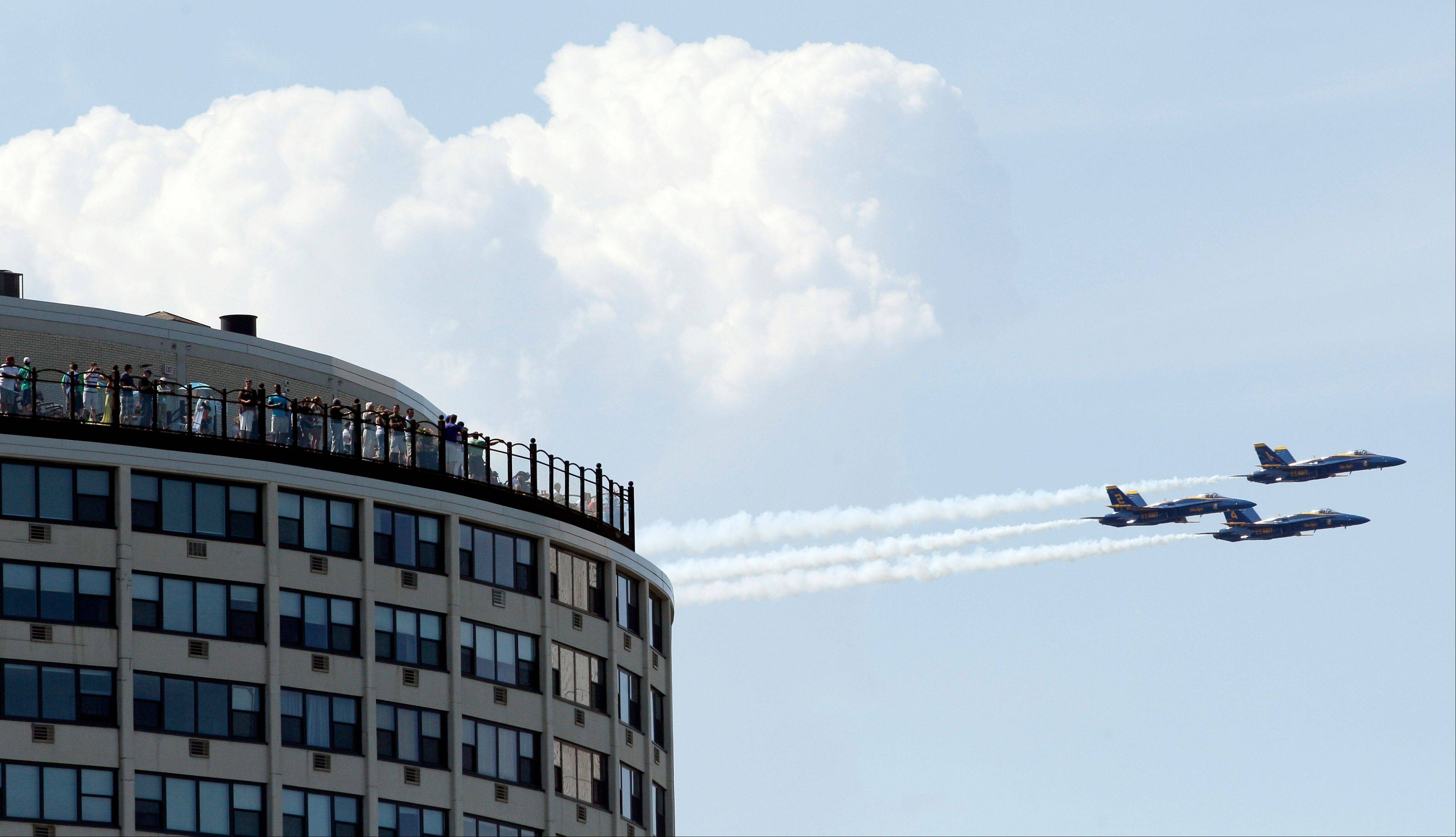 People watch the U.S. Navy Blue Angels perform over Lake Michigan during the Chicago Air and Water Show on Sunday, Aug. 19, 2012, in Chicago.