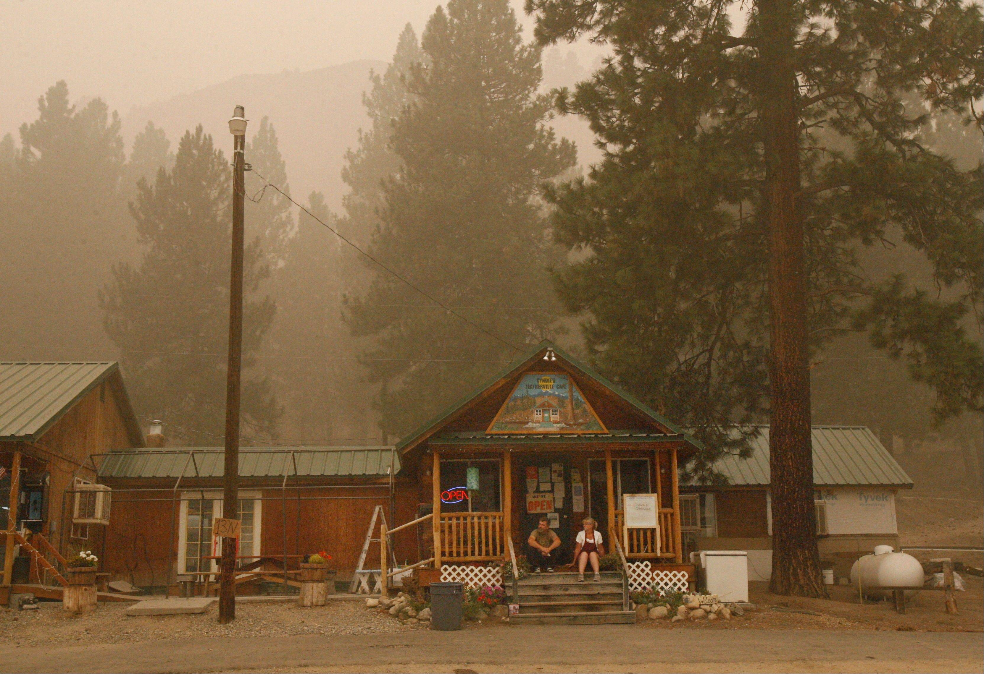 "Pat Christensen, left, and his wife Cyndie sit on the steps of the Featherville Cafe Saturday Aug. 18, 2012 as smoke from Trinity Ridge fire engulfs the area. ""I'm not leaving till I see flames come over the top,"" says Pat Christensen, left, referring to the ridge behind Cyndie's Featherville Cafe. Pat and his wife, Cyndie, are the owners of the cafe in Featherville, Idaho. Elmore County Sheriff's deputies issued mandatory evacuation orders to residents of Featherville on Saturday, Aug. 18, 2012, because of the Trinity Ridge fire. The Christensens stayed to keep their generators running, which keep the cafe's prime rib, hamburgers and meat frozen. ""We'll be open,"" says Pat."