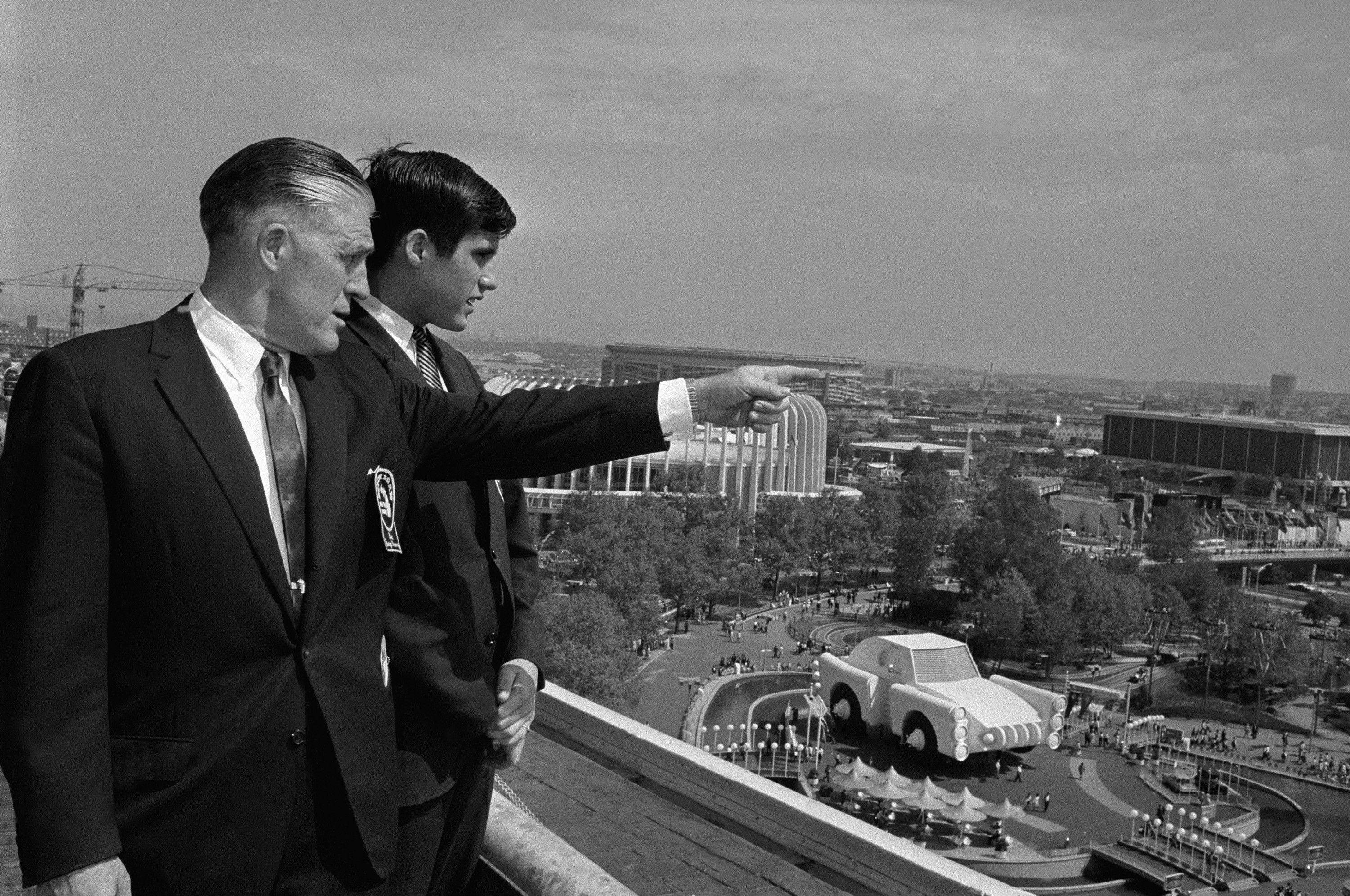 Gov. George Romney and his son, Mitt, look out over the New York World's Fair grounds from the heliport after attending a Michigan breakfast at the Top of the Fair Restaurant.