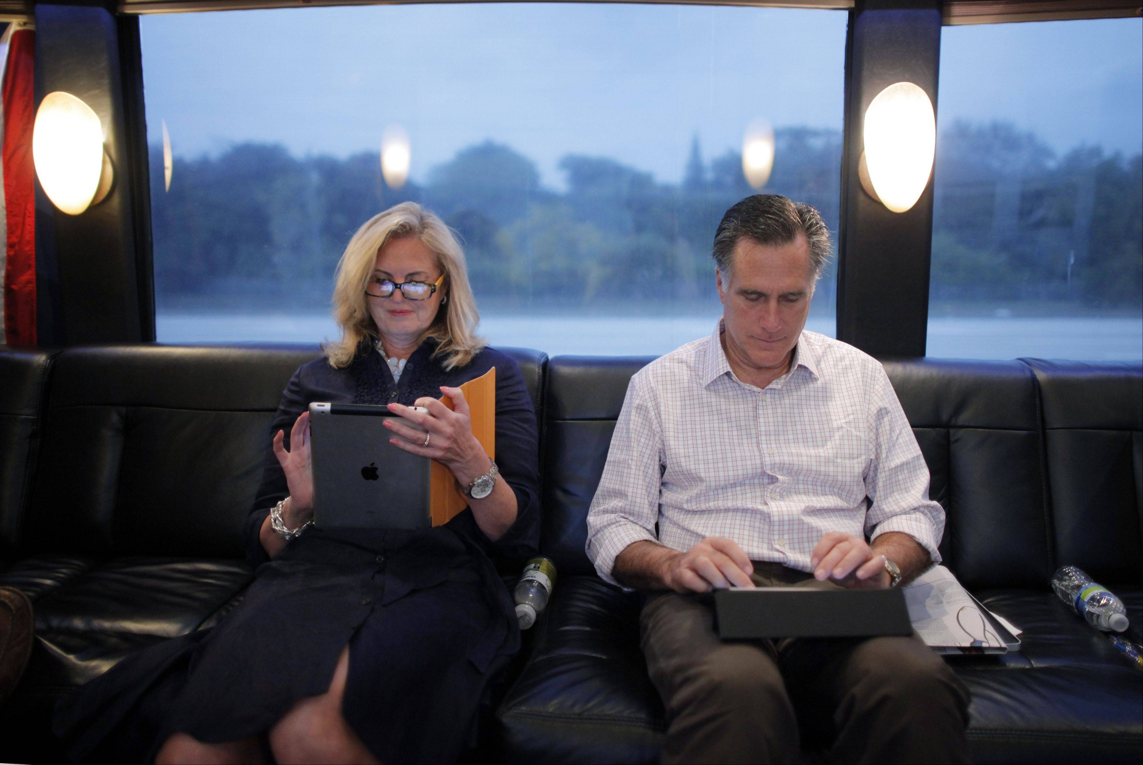 In this Jan. 29, 2012, file photo, Republican presidential candidate, former Massachusetts Gov. Mitt Romney, and his wife Ann work on their iPads on their campaign bus as it travels to Hialeah, Fla.