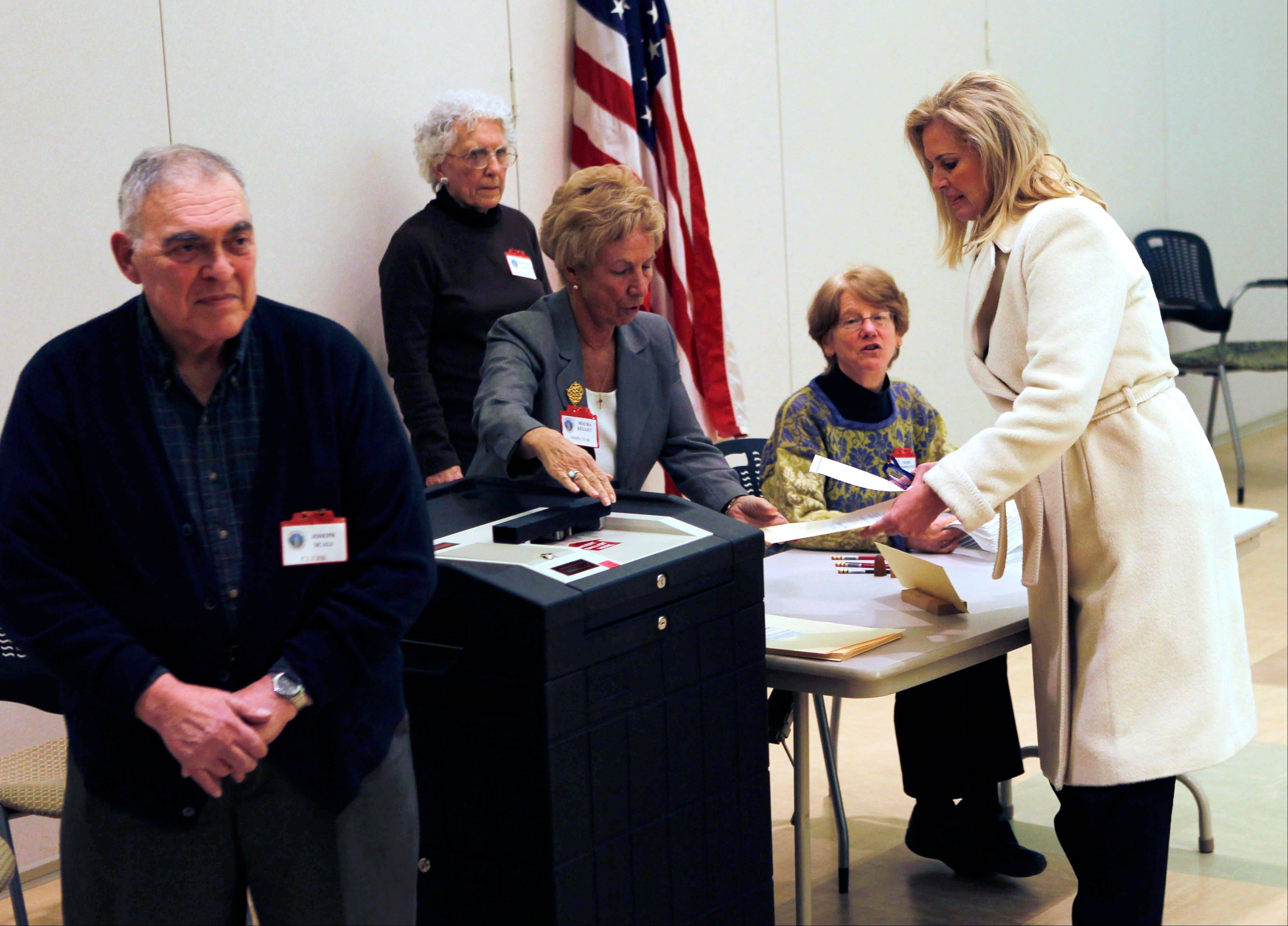 In this March 6, 2012, photo, Ann Romney, wife of Republican presidential candidate former Massachusetts Gov. Mitt Romney votes in the Super Tuesday Massachusetts primary at the Beech Street Senior Center in Belmont, Mass., as Maryann Scali, who served with Ann on the Belmont Town Meeting together, watches. Husband Joe Scali is at front left.