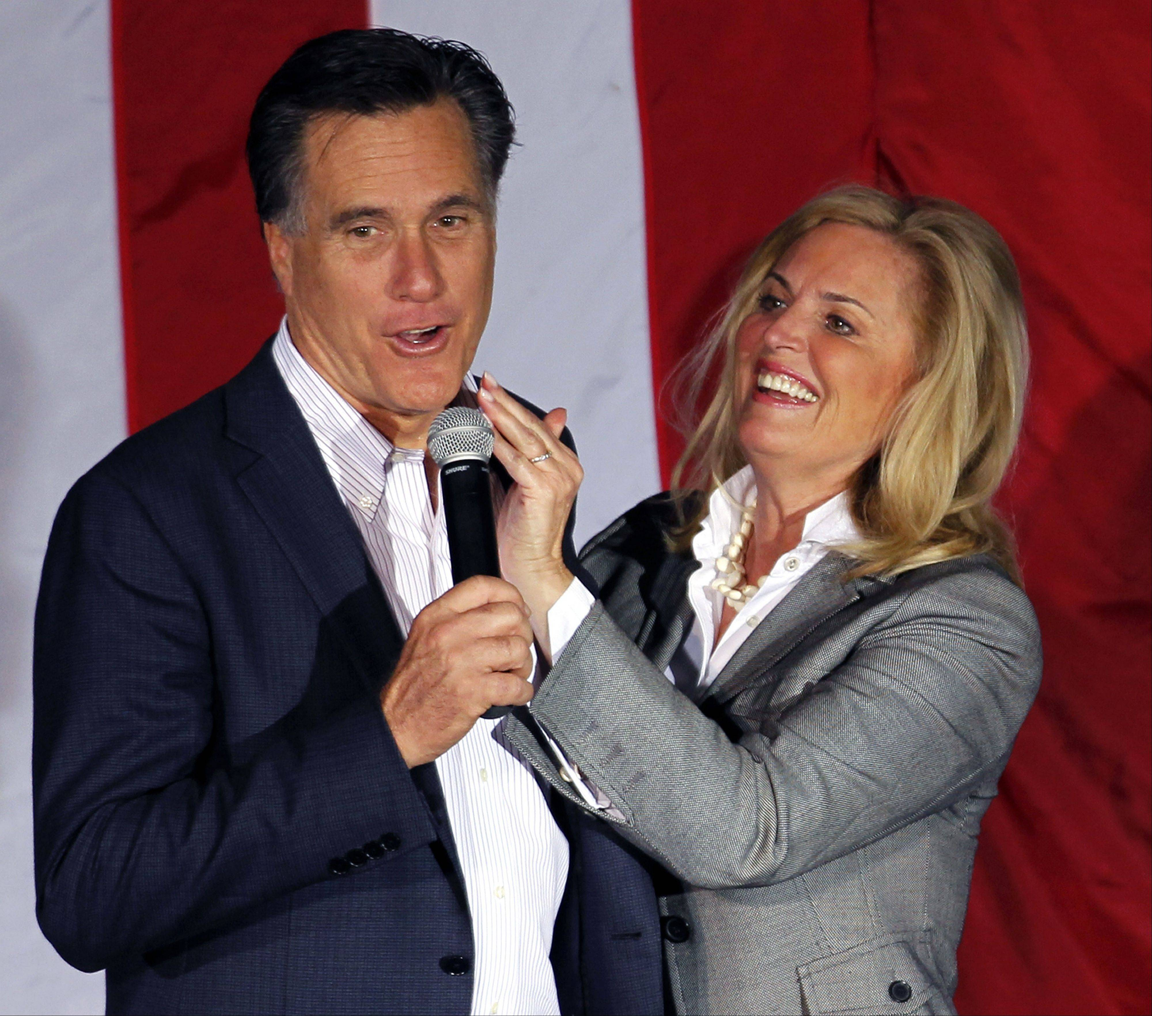 In this March 5, 2012, file photo, Ann Romney, wife of Republican presidential candidate, former Massachusetts Gov. Mitt Romney, wipes lipstick off his face after kissing him at a campaign rally in Zanesville, Ohio.