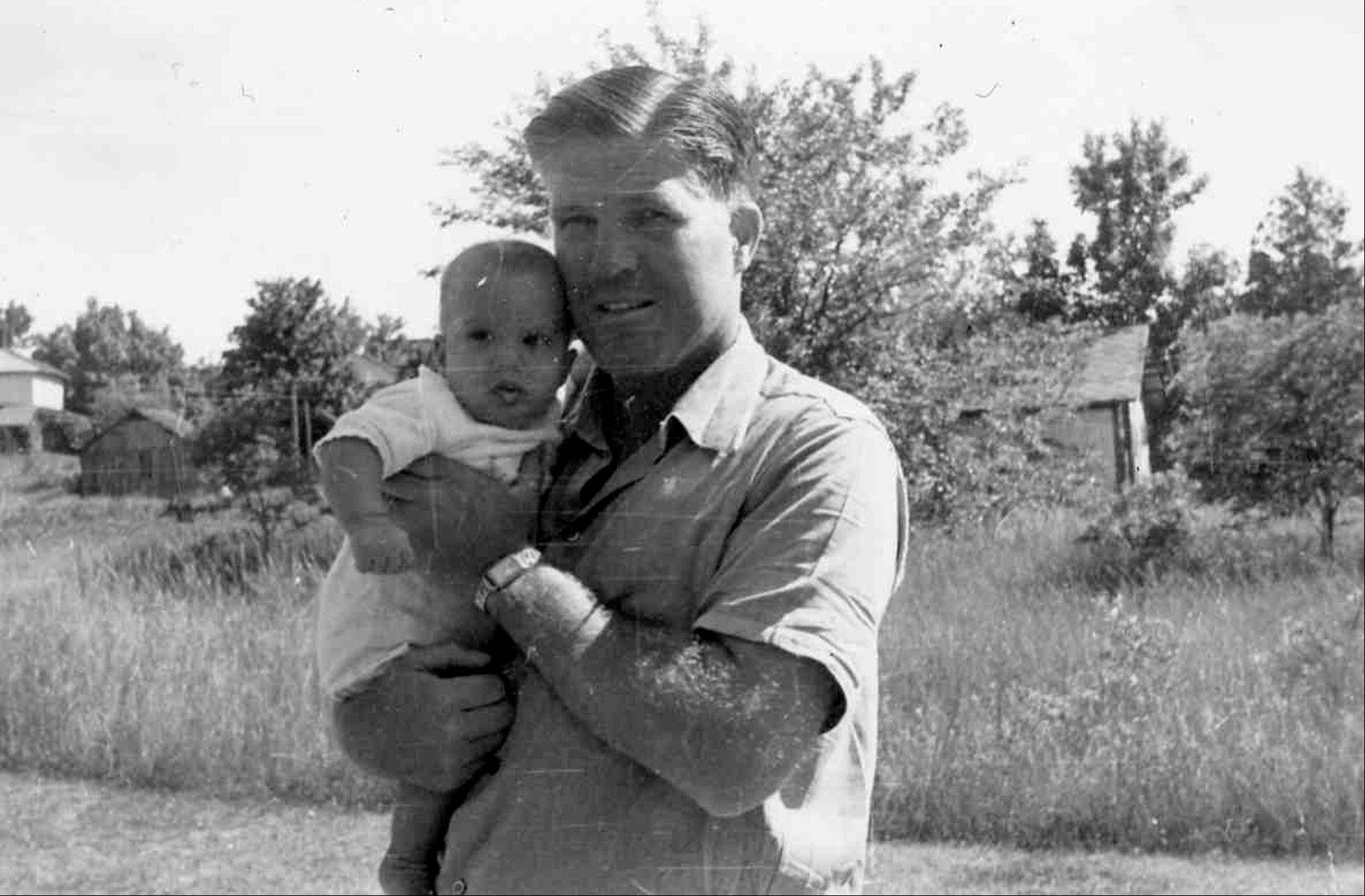 This 1947 photo provided by the Romney for President, Inc., location unknown, shows his father George Romney holding Mitt, who was born earlier that year. Long before Mitt Romney became the millionaire candidate from Massachusetts, he was his father' son, weeding the garden in the upscale suburb of Detroit where he grew up. He hated the chore. But he idolized the man who made him do it - George Romney, the outspoken, no-nonsense, auto executive turned politician.