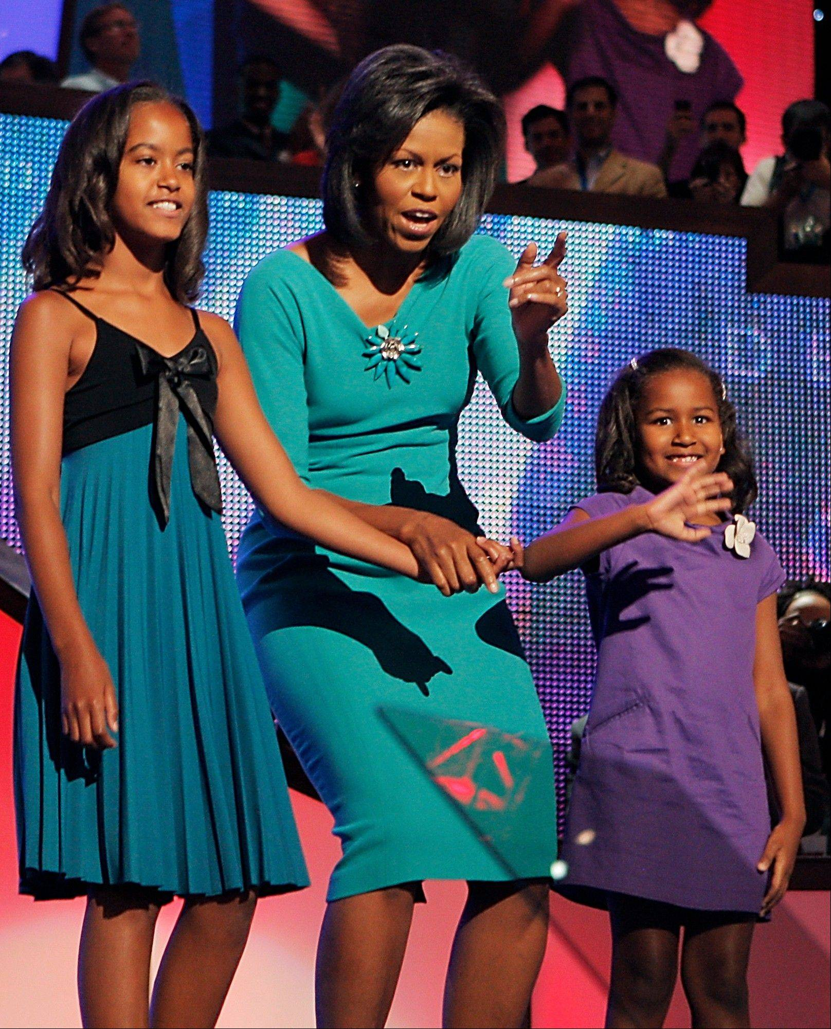In this Aug. 25, 2008, file photo, Michelle Obama, wife of then-Democratic presidential candidate, Sen. Barack Obama, D-Ill., and daughters Malia, left, 10, and Sasha, right, 7, wave to the audience the Democratic National Convention in Denver. She is 5-foot-11, and she is world-famous. Sometimes she inspires awe in her admirers. She has been accused of being the angry type. So when Michelle Obama meets people, she likes to bring things down to earth with a hug.