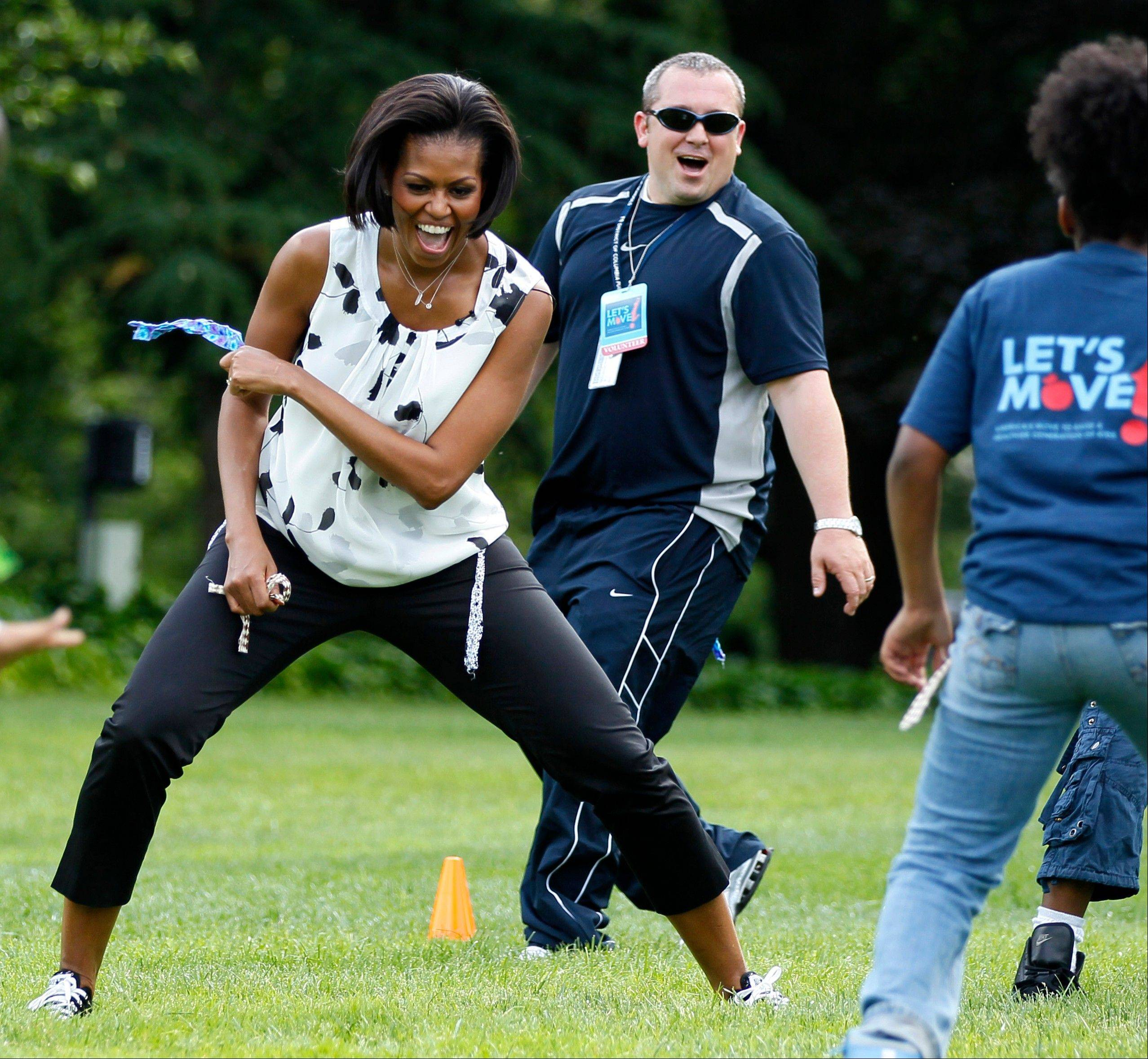In this May 25, 2010, file photo first lady Michelle Obama plays with kids at an event on the South Lawn of the White House, in Washington. She is 5-foot-11, and she is world-famous. Sometimes she inspires awe in her admirers. She has been accused of being the angry type. So when Michelle Obama meets people, she likes to bring things down to earth with a hug.