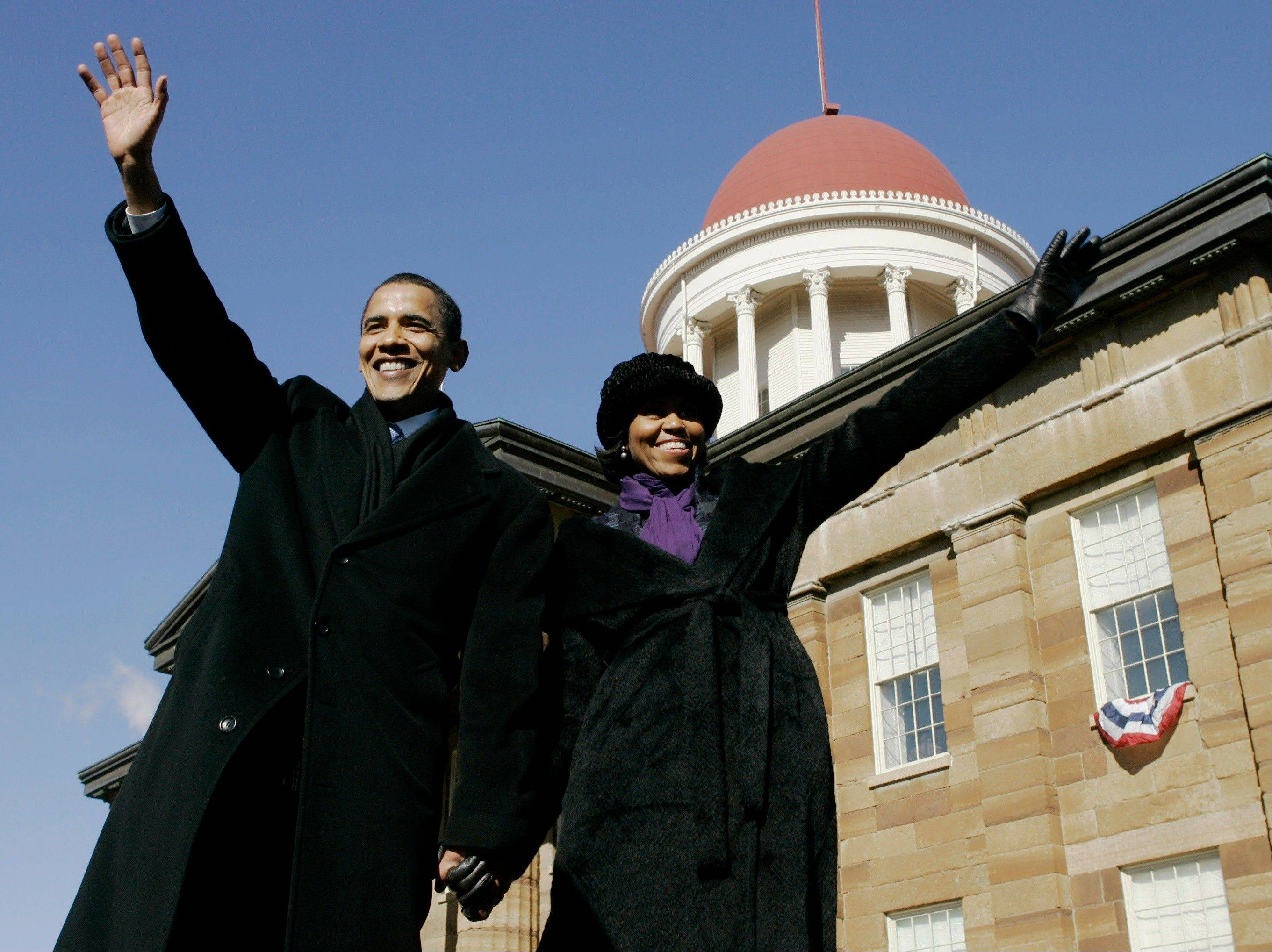 In this Feb. 10, 2007, file photo, then-Sen. Barack Obama, D-Ill., and his wife Michelle wave to the crowd after he announced his candidacy for president of the United States at the Old State Capitol in Springfield, Ill. She is 5-foot-11, and she is world-famous. Sometimes she inspires awe in her admirers. She has been accused of being the angry type. So when Michelle Obama meets people, she likes to bring things down to earth with a hug.