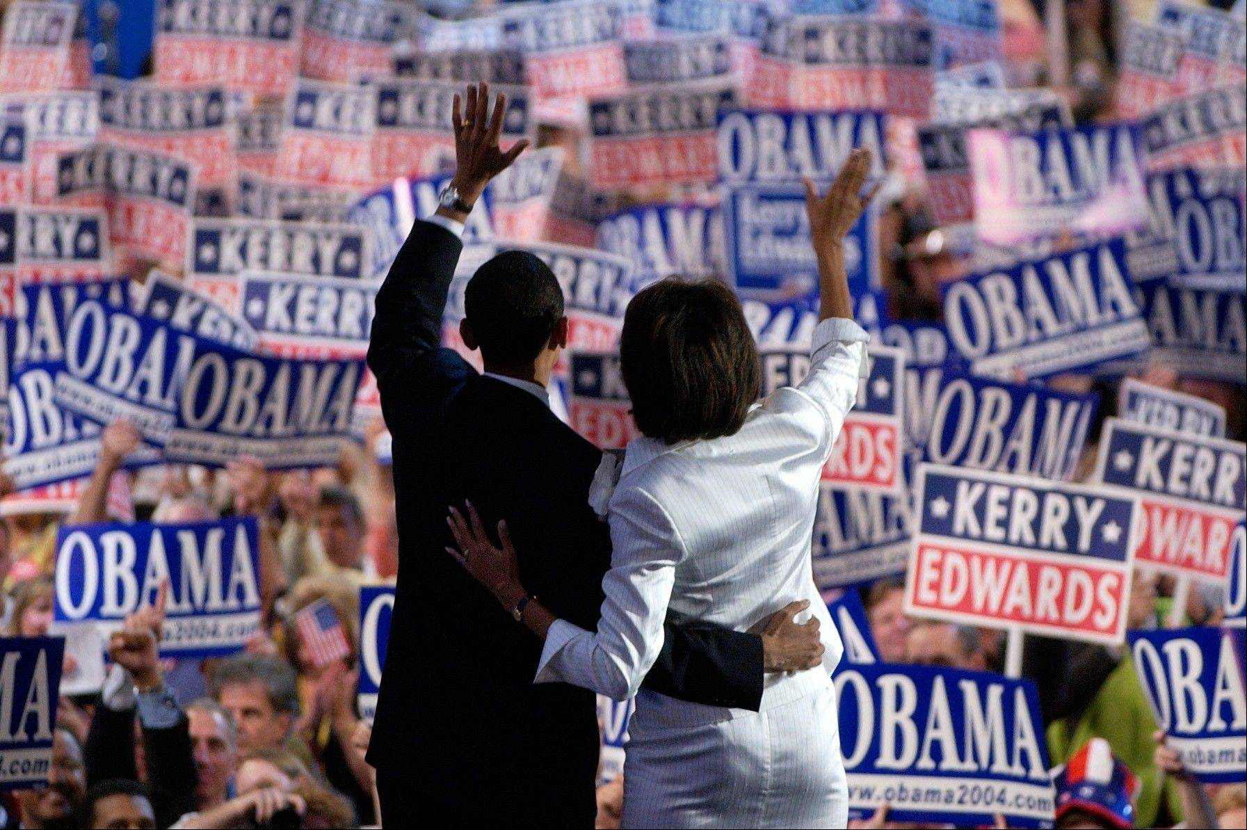 In this July 27, 2004, file photo,Barack Obama, candidate for U.S. Senate from Illinois, and his wife Michelle wave to delegates after he delivered his keynote address to the Democratic National Convention in Boston in this July 27, 2004, file photo. She is 5-foot-11, and she is world-famous. Sometimes she inspires awe in her admirers. She has been accused of being the angry type. So when Michelle Obama meets people, she likes to bring things down to earth with a hug.