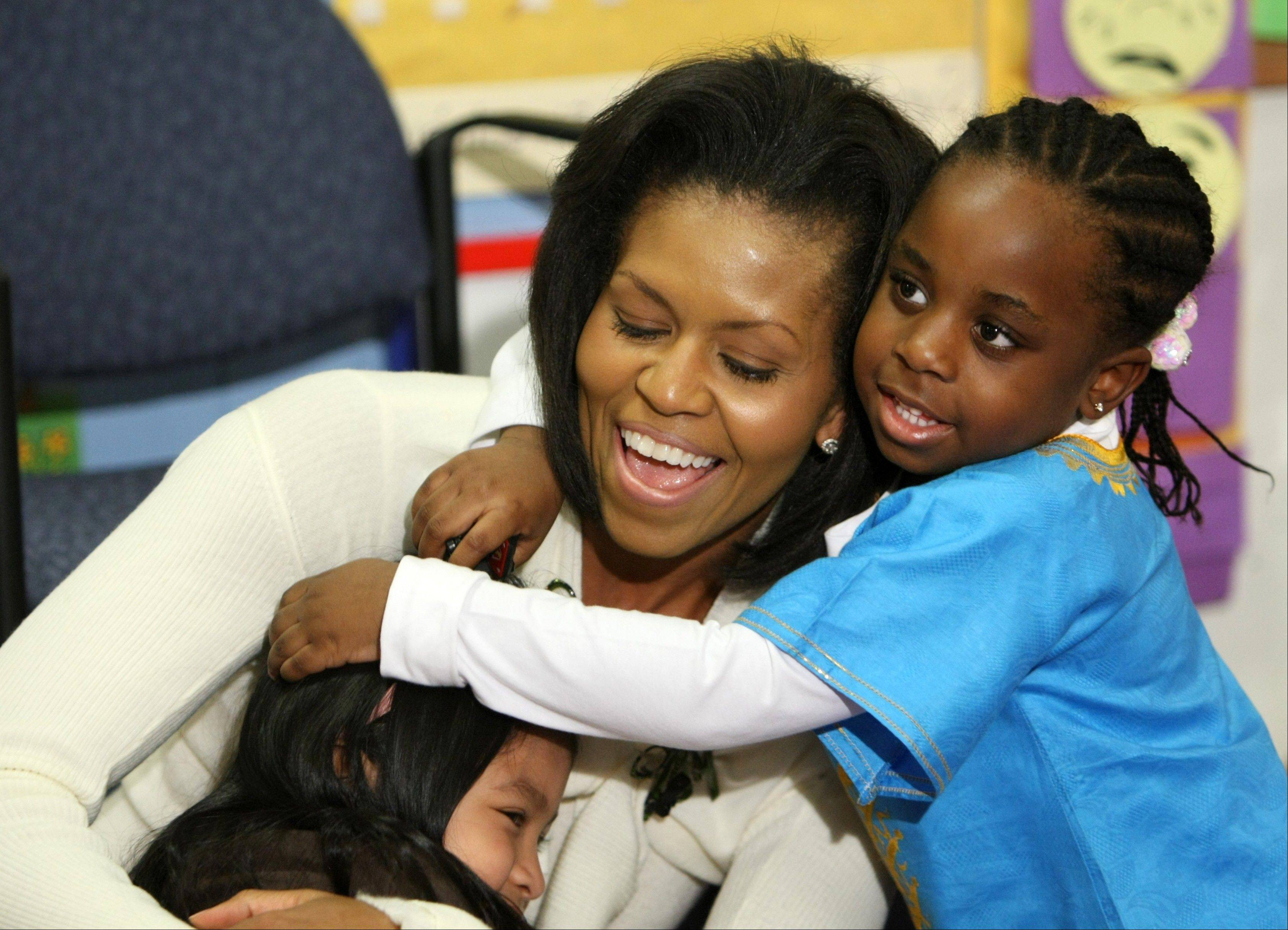 In this Feb. 10, 2009, file photo, first lady Michelle Obama hugs children after reading a book at Mary's Center in Washington. She is 5-foot-11, and she is world-famous. Sometimes she inspires awe in her admirers. She has been accused of being the angry type. So when Michelle Obama meets people, she likes to bring things down to earth with a hug.