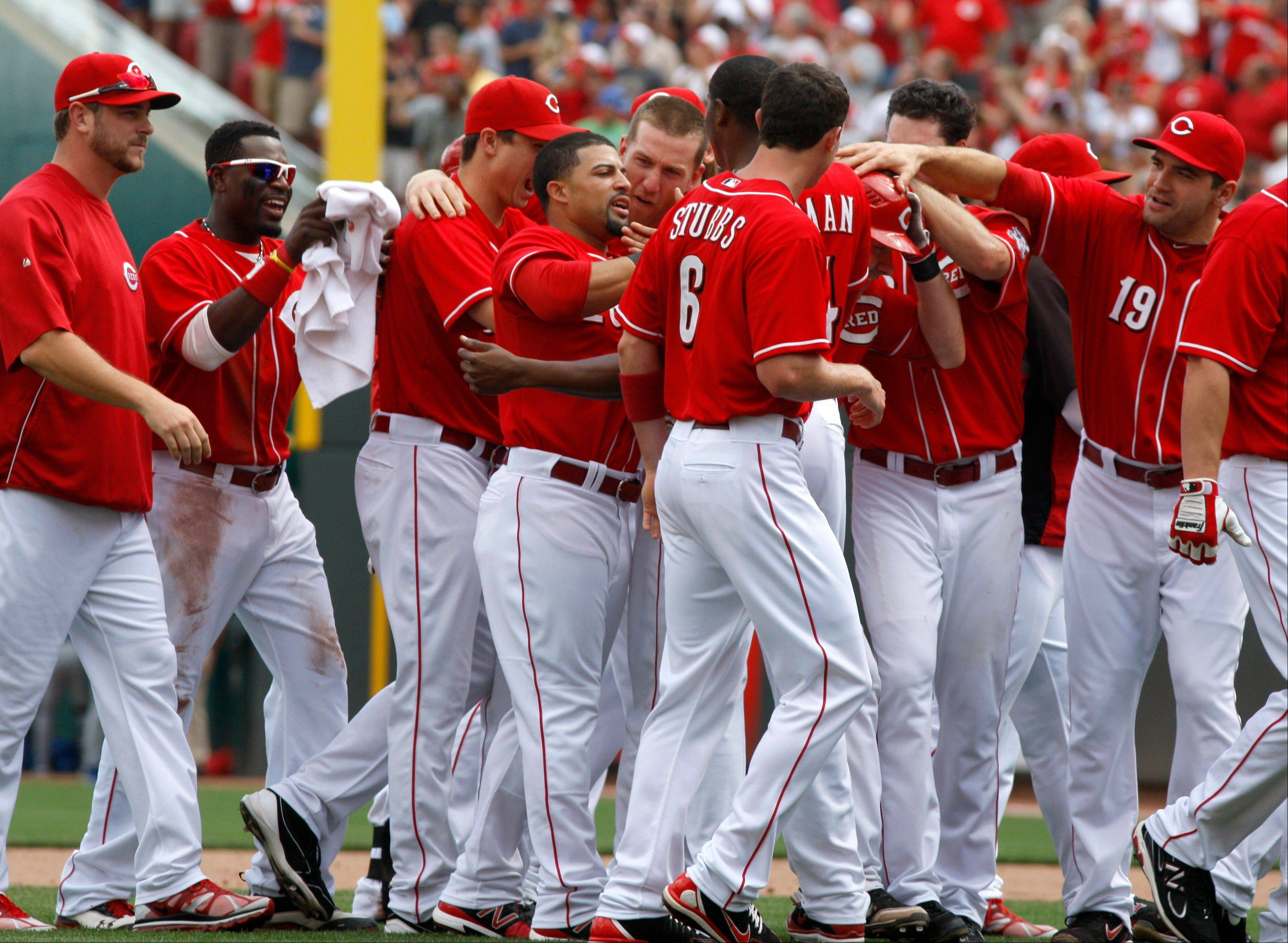 The Cincinnati Reds' Xavier Paul, fourth from left, is congratulated by teammates after the Reds defeated the Cubs 5-4 Sunday in Cincinnati.