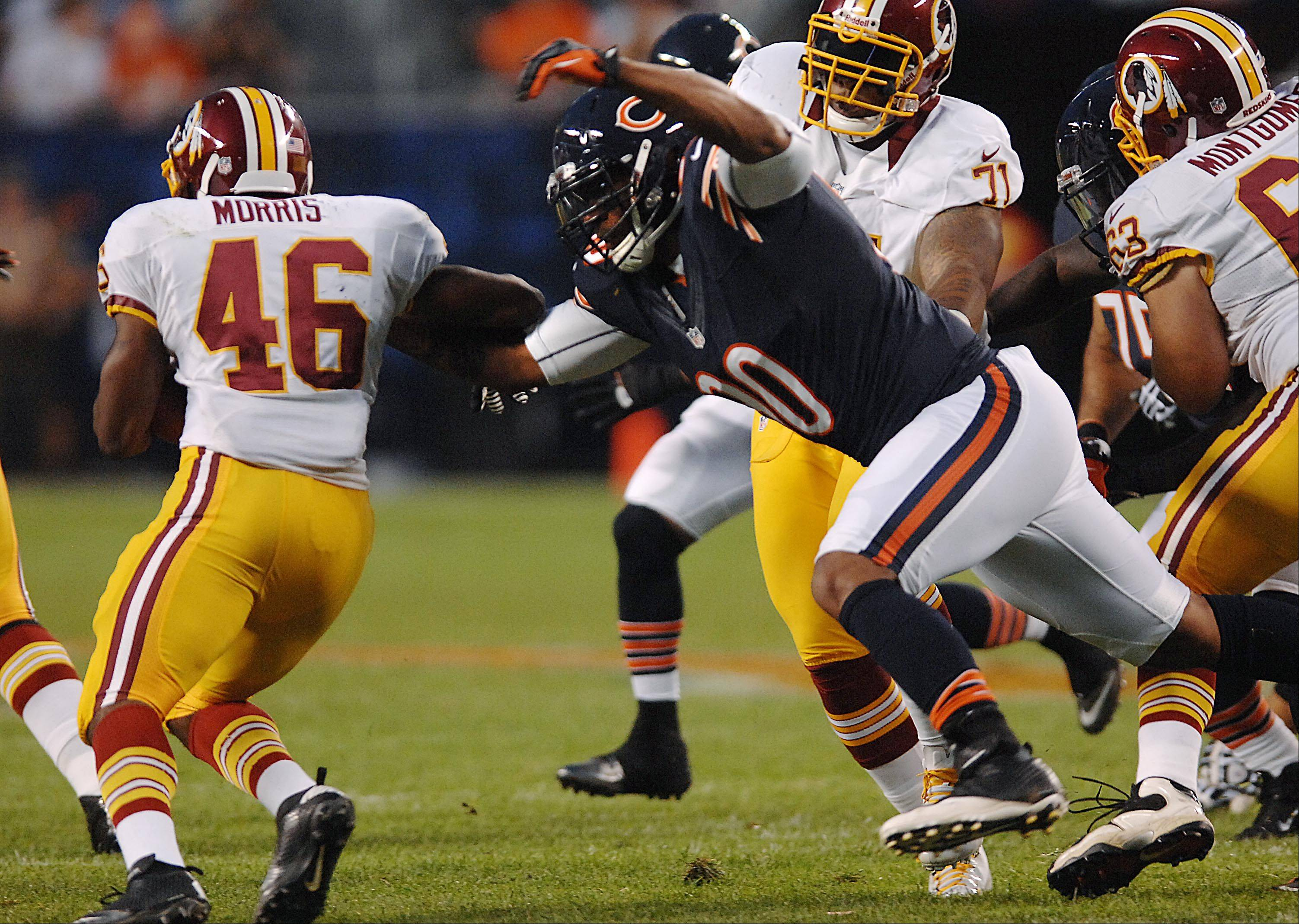 Chicago Bears defensive end Julius Peppers reaches Washington Redskins running back Alfred Morris Saturday in the second preseason game at Soldier Field in Chicago.