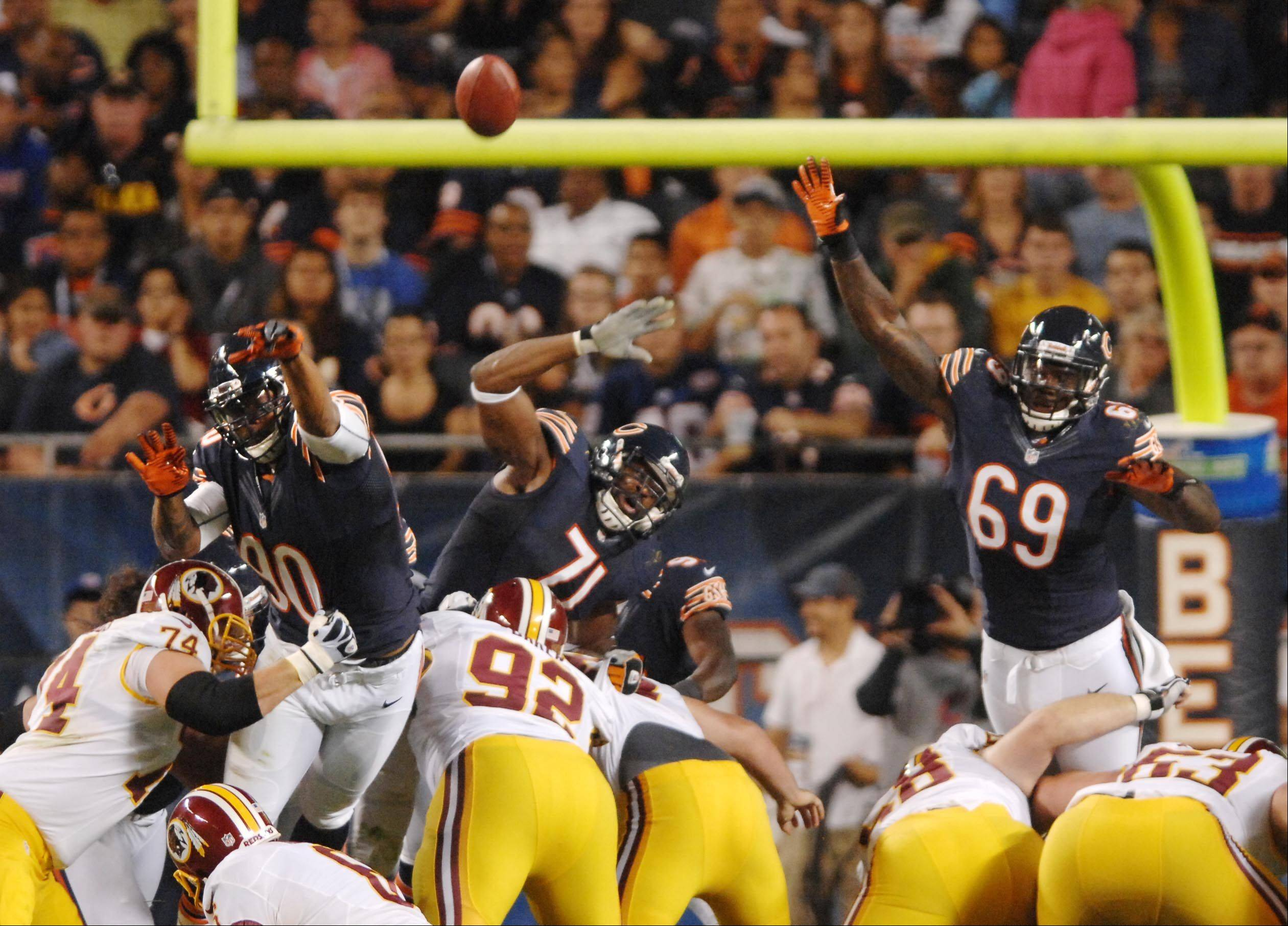 Chicago Bears defensive end Julius Peppers, defensive end Israel Idonije, and defensive end Henry Melton try to block a field goal Saturday against the Washington Redskins in the second preseason game at Soldier Field in Chicago.