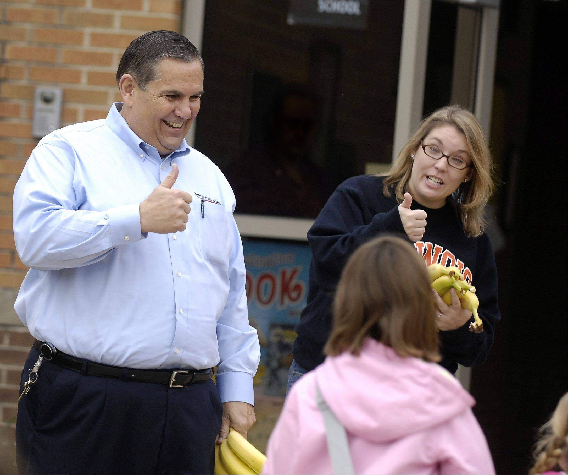 Batavia schools Superintendent Jack Barshinger and volunteer Jaime Schumacher gives the thumbs-up — and bananas — to Alice Gustafson Elementary School students who walked or biked to school in honor of International Walk to School month, in 2009. Barshinger announced Monday he will retire at the end of the school year.
