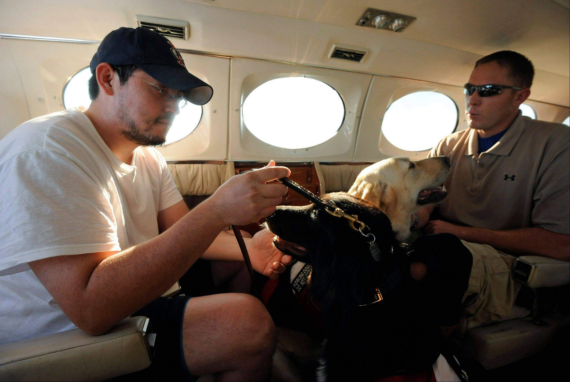 Luis Zaragoza, of Chicago, and Jason O. Brown of Murphysboro fly above Carbondale as part of a training exercise to practice flying with their service dogs, Cheyenne and Tonka, in Carbondale.