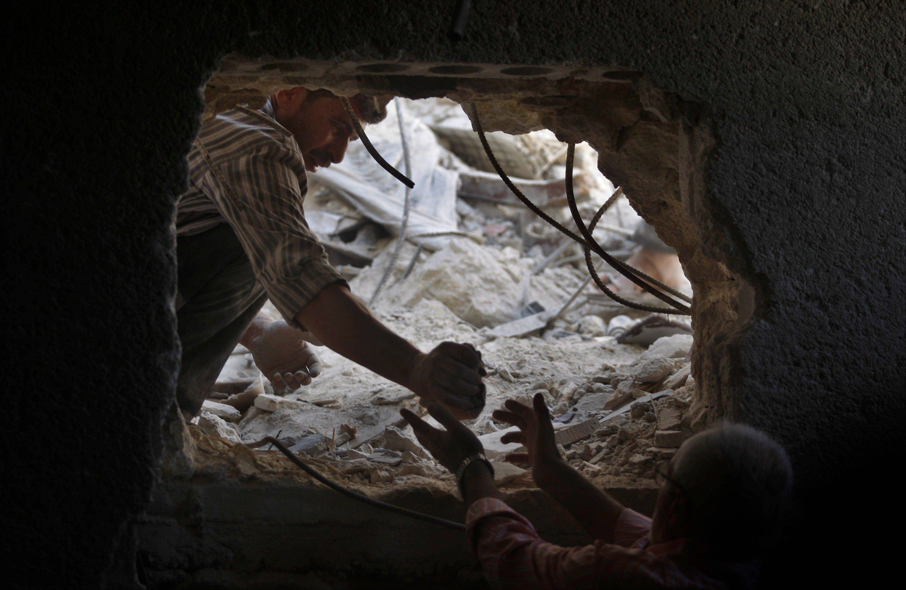 Syrians look for the bodies of two girls thought to be under the rubble of a building hit by a Syrian government airstrike in Aleppo, Syria, on Sunday.
